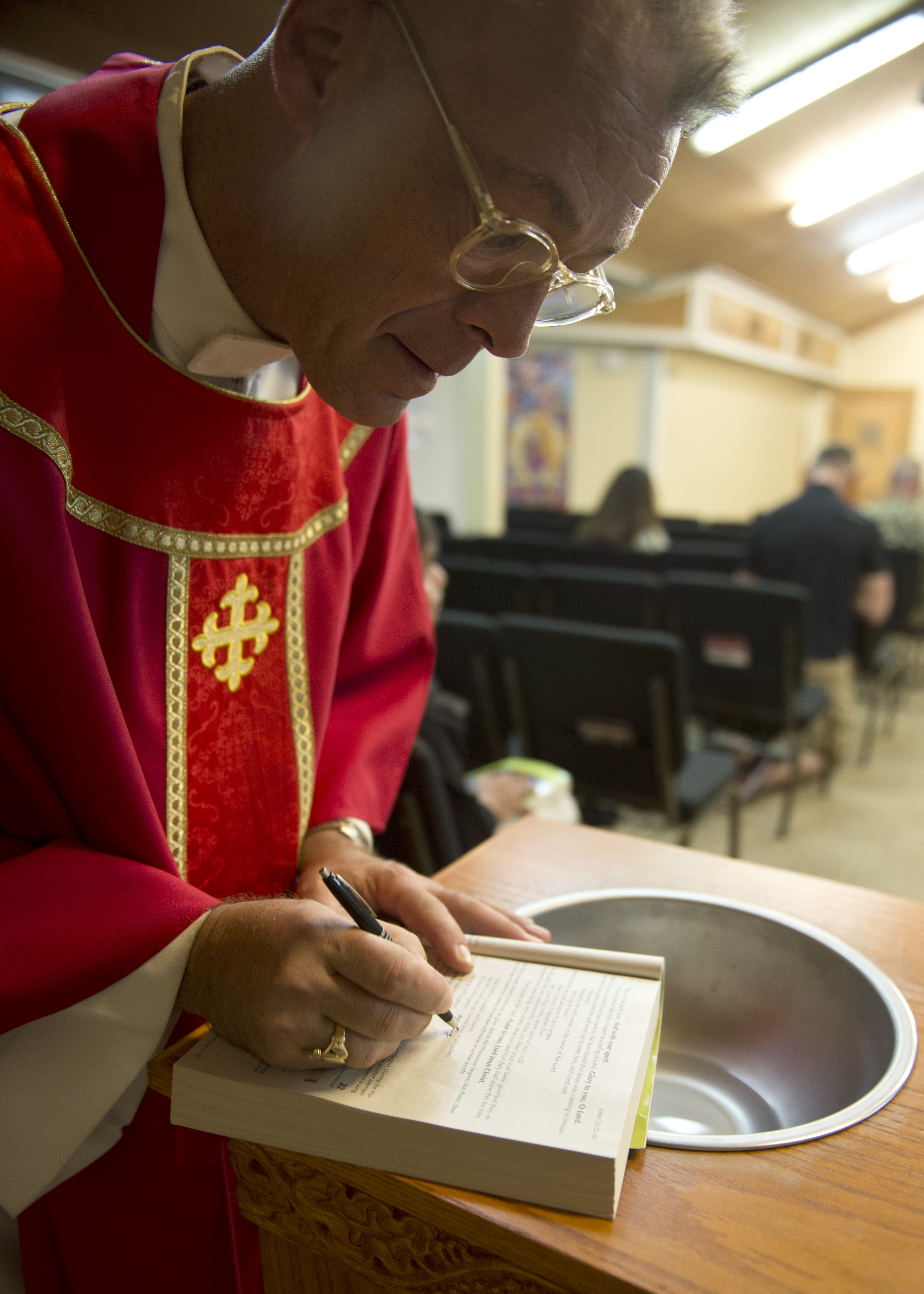 U.S. Navy Chaplain Capt. Sean O'Brien looks through his bible prior to Catholic mass at Camp Lemonnier, Djibouti, Mar. 28, 2015. The Chaplain's priorities are to enhance Airmen's readiness by preparing them with spiritual resiliency, engaging them through ministry of presence and spiritual care and ensuring worship and religious education opportunities are available to all. (U.S. Air Force photo by Staff Sgt. Kevin Iinuma)