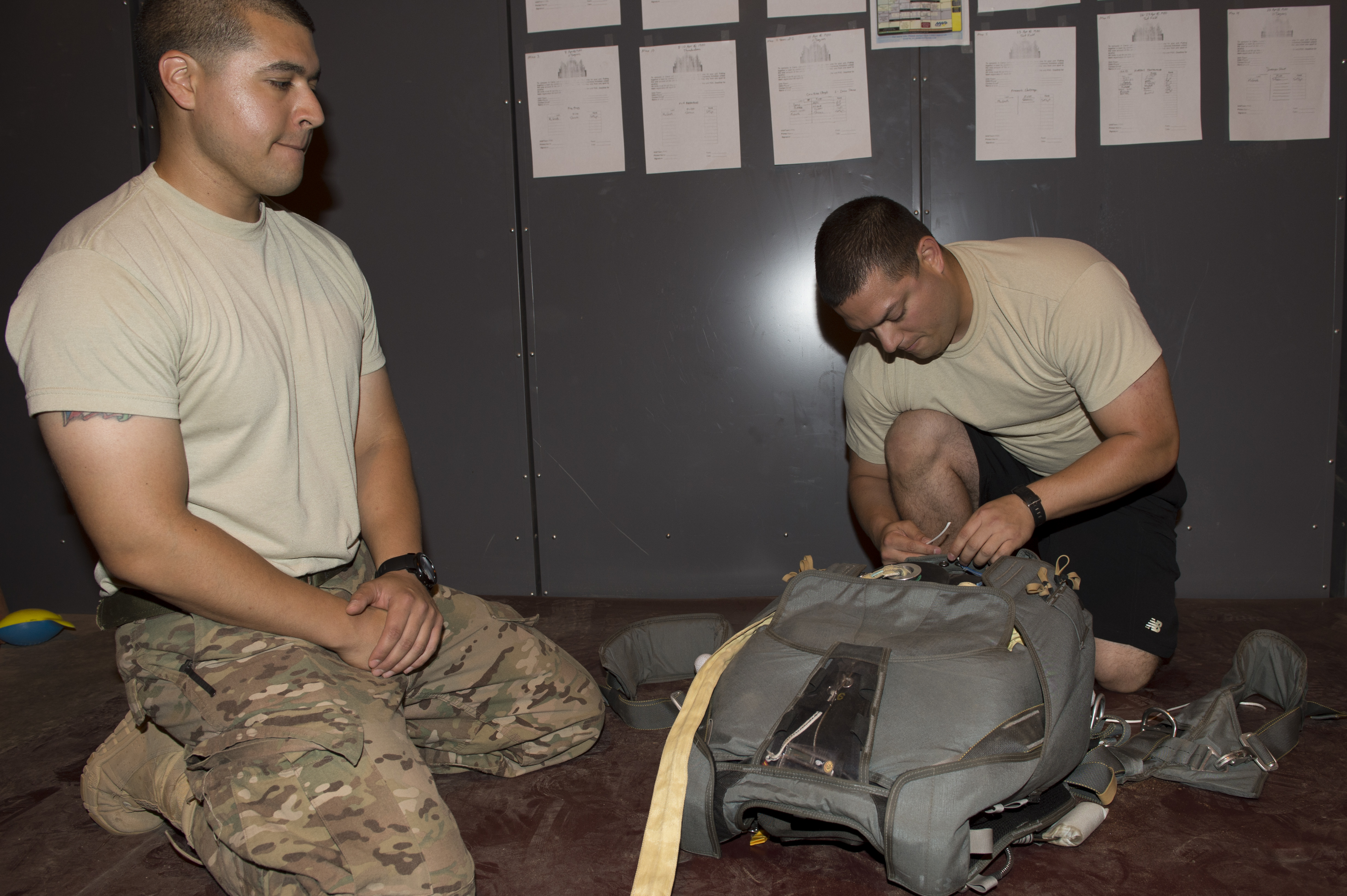 "(Left) U. S. Air Force Tech. Sgt. Isaac Corniel, 82nd Expeditionary Rescue Squadron Aircrew Flight Equipment rigger non-commissioned officer–in-charge, waits to do the final inspection after Senior Airman Victor Diaz, secures the final flaps of the parachute at Camp Lemonnier, Djibouti, Mar. 26, 2015. The NCOIC will preform what is called a ""Rigger Check"", which is a quality inspection point that ensures a good chute. (U.S. Air Force photo by Staff Sgt. Carlin Leslie)"