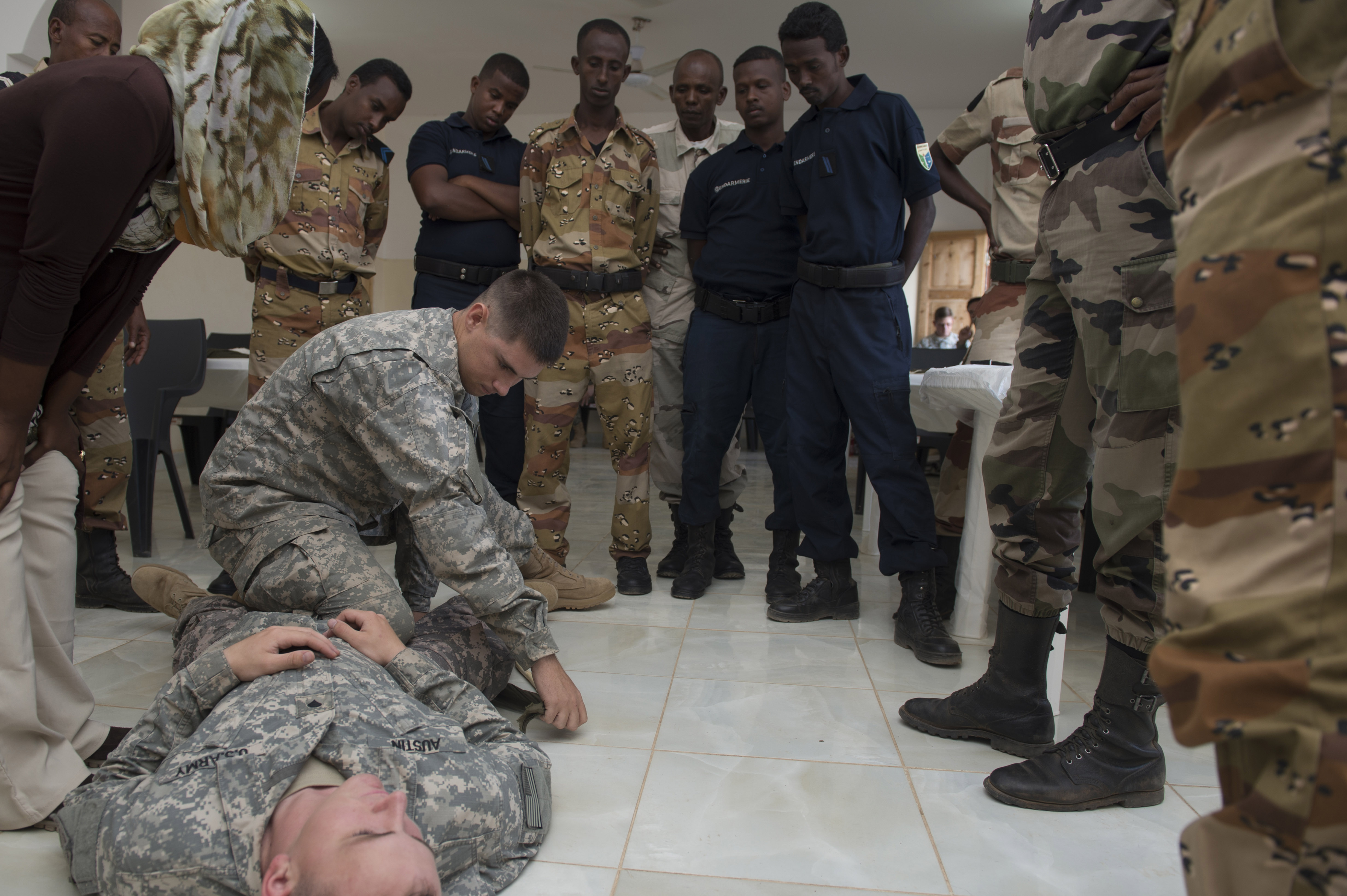 Specialist Dillion Flowers, 1-77 Armored Regiment health care specialist, demonstrates the way the U.S. Army trains to apply a tourniquet to the Djibouti Gendarmerie, during the First Aid Best Practice Exchange between, the Djibouti Gendarmerie, 404th and 407th Civil Affairs Battalions and the 1-77 Armored Regiment health care specialists in Cheik Moussa, Djibouti, Apr. 4, 2015. (U.S. Air Force Photos by Staff Sgt. Carlin Leslie)