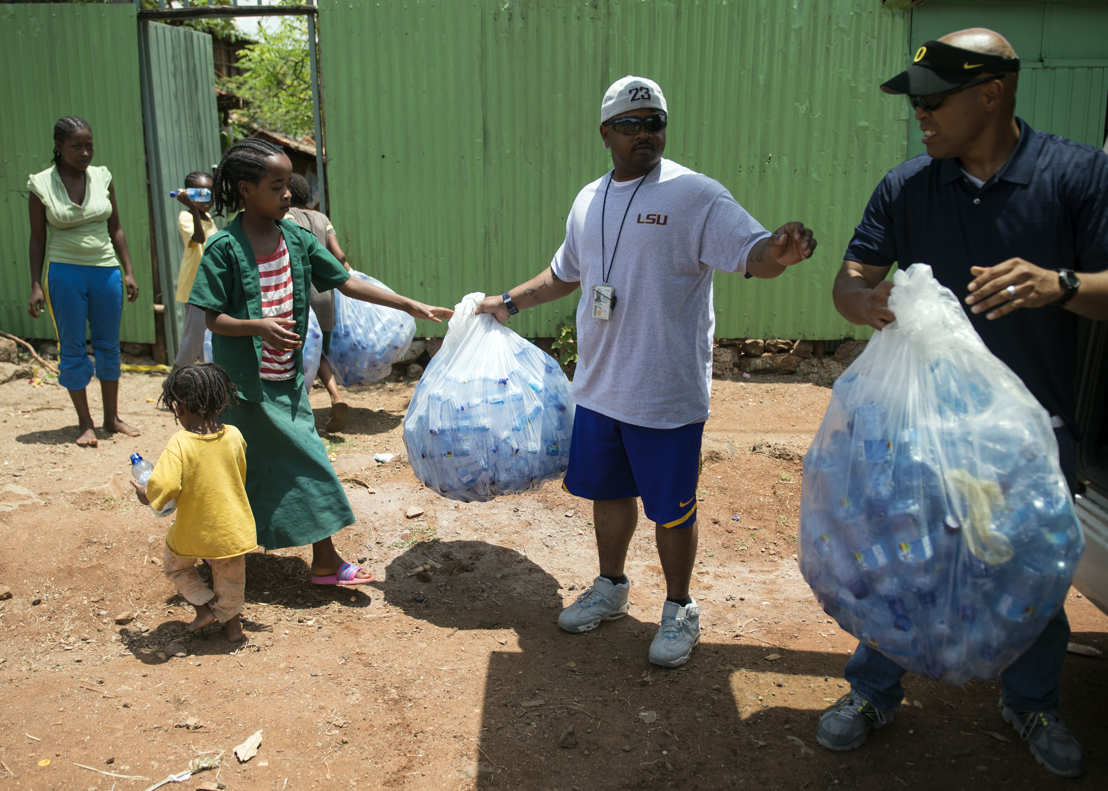From right, U.S. Army Chaplain (Maj.) Lawrence Allison, Combined Joint Task Force-Horn of Africa Religious Affairs deputy director, and U.S. Navy Petty Officer 2nd Class Rory Carmouche, CJTF-HOA Religious Programs Specialist, hand out bags of empty bottles to an orphanage in the CJTF-HOA area of responsibility, Apr. 3, 2015. The empty water bottles will be used by the orphans to fill with water and use as a drinking containers due to limited resources. (U.S. Air Force photo by Staff Sgt. Kevin Iinuma)