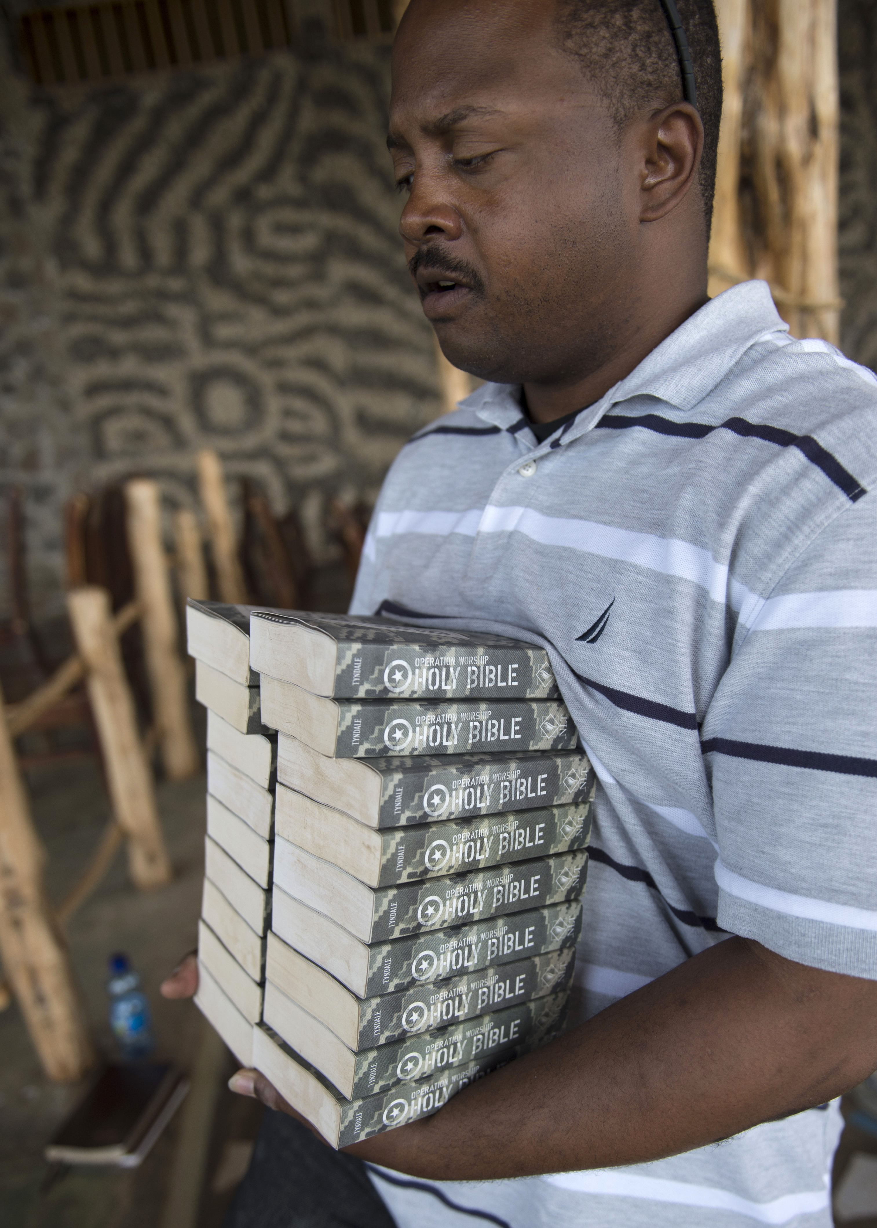 U.S. Navy Petty Officer 2nd Class Rory Carmouche, Combined Joint Task Force-Horn of Africa Religious Programs Specialist, gathers Bibles for Easter service on Apr. 5, 2015 for members in the CJTF-HOA area of responsibility.  As a Religious Programs Specialist, Carmouche provides religious and administration assistance for the chaplains. (U.S. Air Force photo by Staff Sgt. Kevin Iinuma)