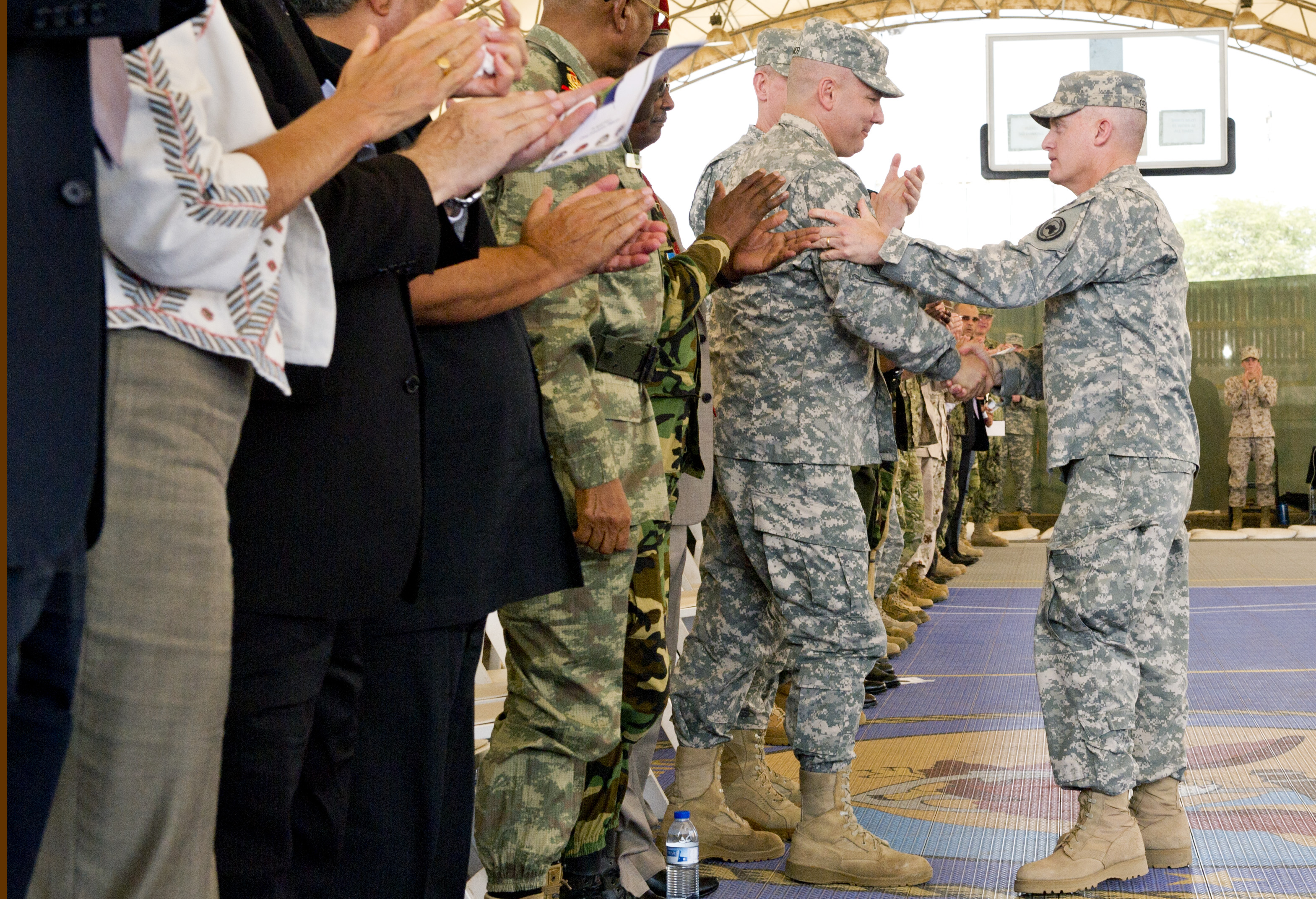 Maj. Gen. Wayne W. Grigsby Jr., the former commander of Combined Joint Task Force Horn of Africa, congratulates Maj. Gen Mark R. Stammer, on becoming the CJTF-HOA commander, during the change of command ceremony, Apr. 14, 2015. (U.S. Air Force photo by Technical Sgt. Darrell Dean)
