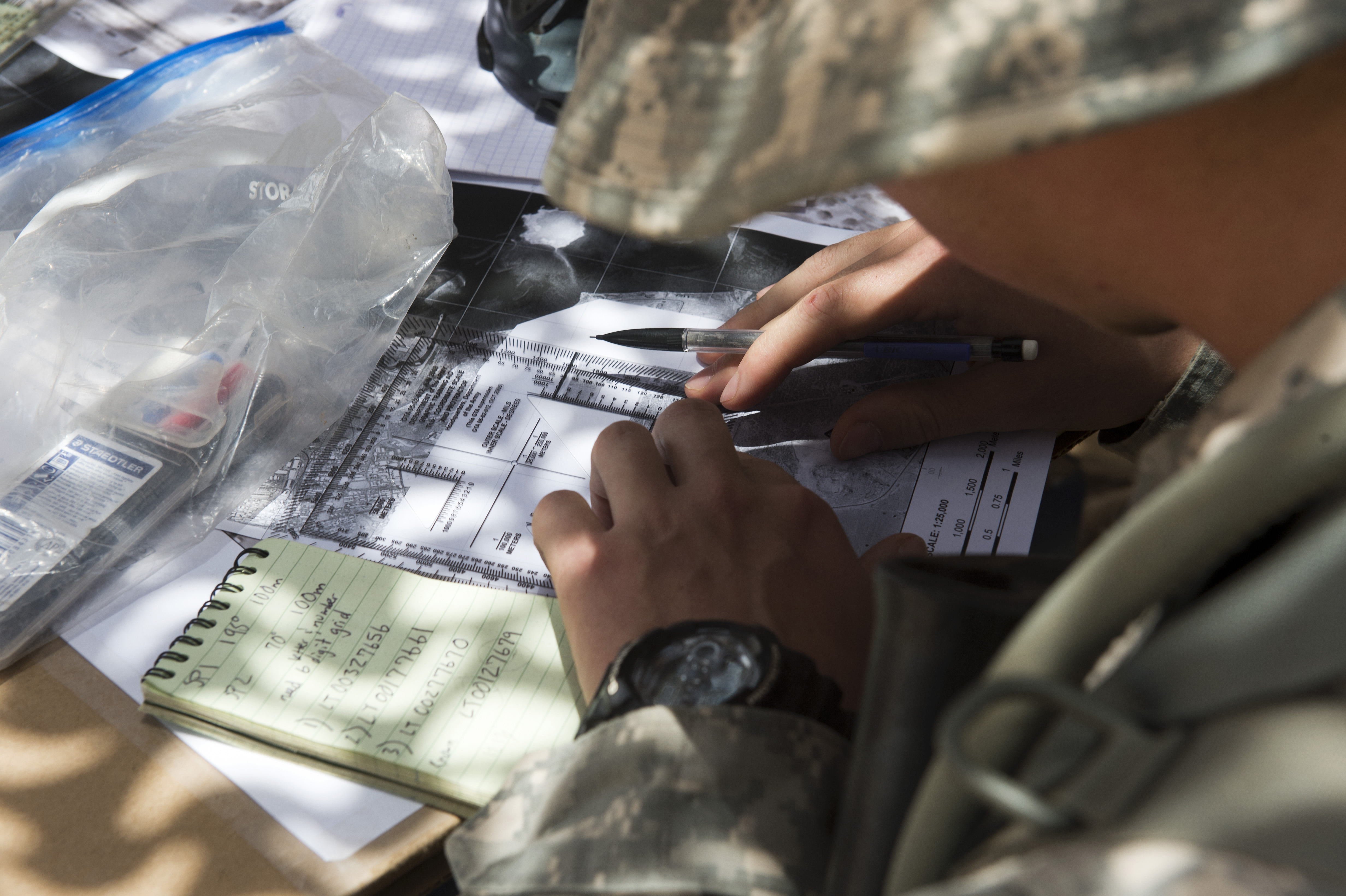 A soldier from the U.S. Army's 1st Battalion, 77th Armor Regiment, plots grid points on a field map during land navigation training on Camp Lemonnier, Djibouti, April 15, 2015. The training was part of the 1/77 AR Rgt. Expert Infantry Badge field training exercises in preparation for the EIB assessment. (U.S. Air Force photo by Staff Sgt. Nathan Maysonet)