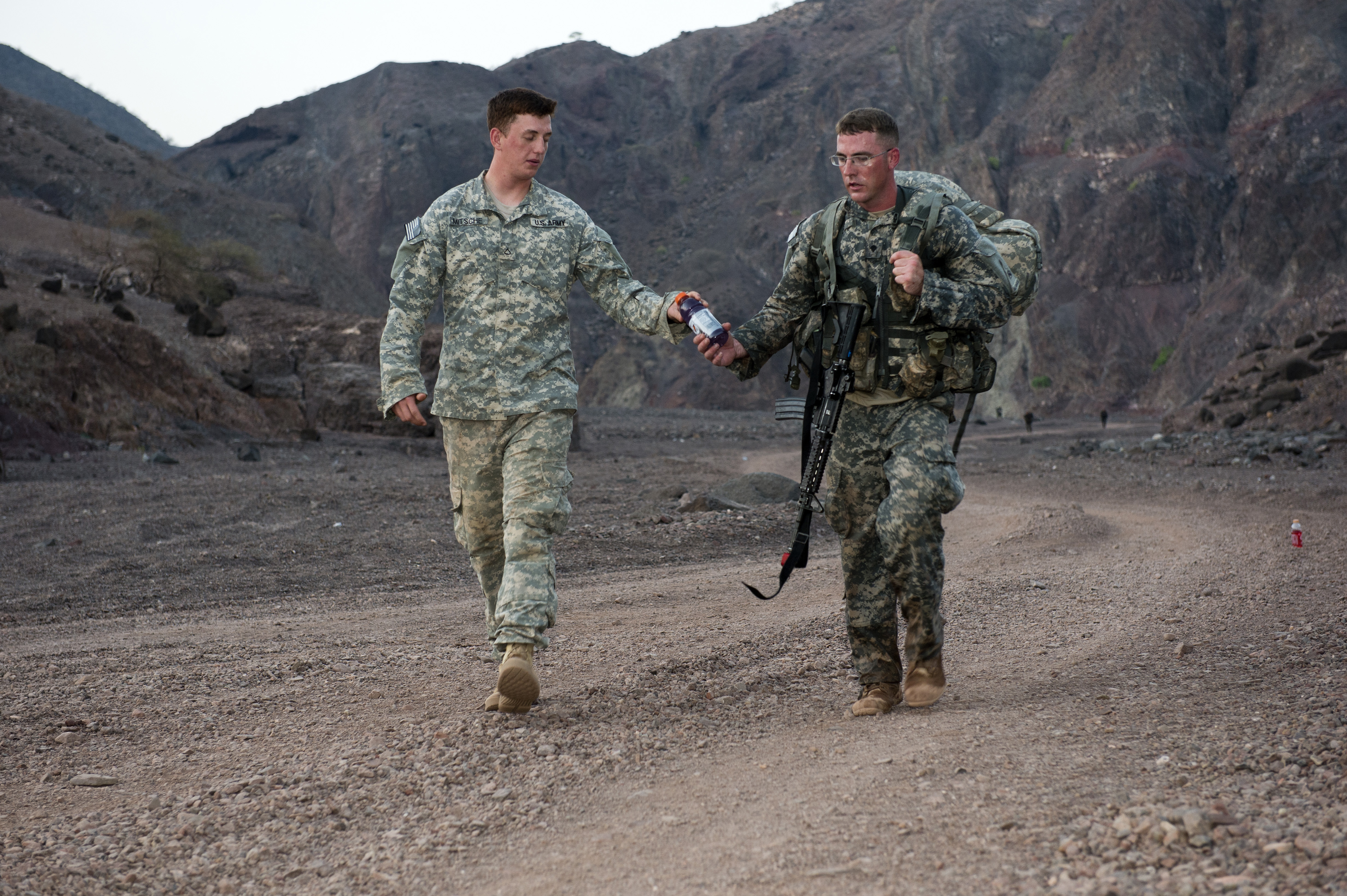 A U.S. Army soldier from the 1st Battalion, 77th Armor Regiment is handed a drink from a fellow 1/77 AR Rgt. Member, during a 12-mile ruck march as part of the Expert Infantry Badge assessment at Arta, Djibouti, April 24, 2015. Candidates for the EIB had to complete the march in less than three hours over unfamiliar terrain to avoid disqualification. (U.S. Air Force photo by Staff Sgt. Nathan Maysonet)