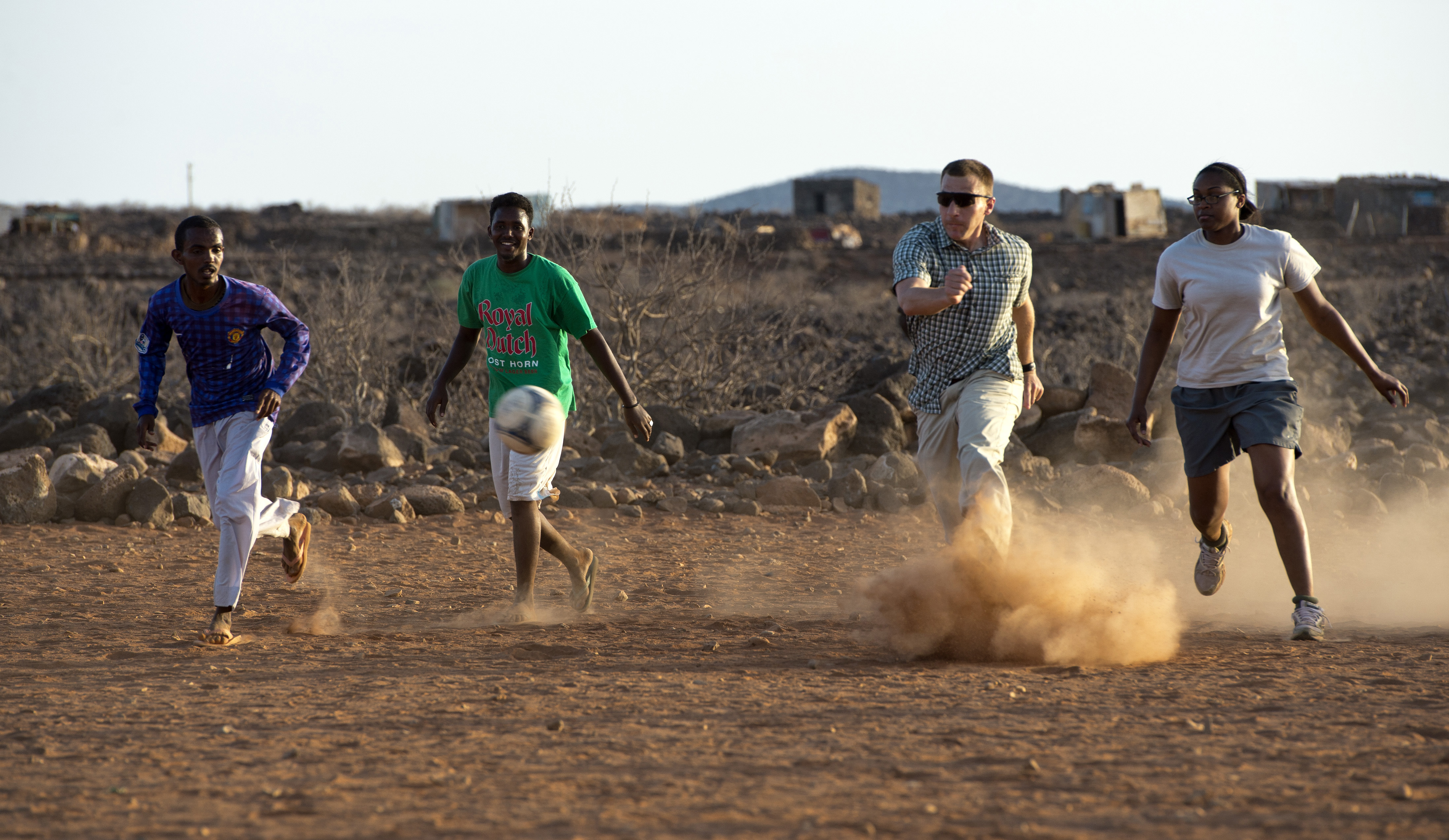 A player for the Combined Joint Task Force-Horn of Africa soccer team kicks the ball during the Chebelley Village Game Night soccer match at Chebelley Village, Djibouti, April 29, 2015. The game began in 2013 and is an event hosted by the U.S. Army's 404th Civil Affairs Battalion. (U.S. Air Force photo by Staff Sgt. Nathan Maysonet)