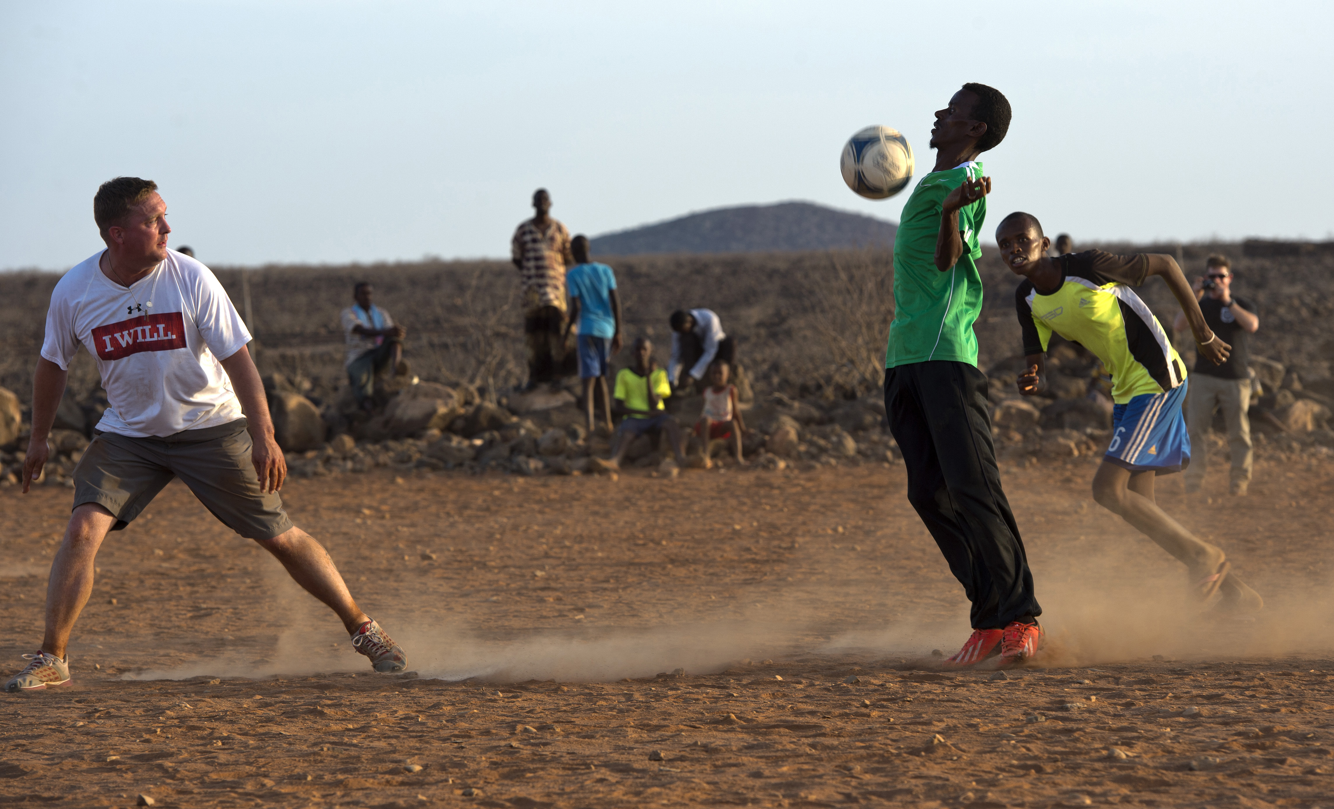 A forward for the Combined Joint Task Force-Horn of Africa soccer team chest blocks a soccer ball during the Chebelley Village Game Night soccer match at Chebelley Village, Djibouti, April 29, 2015.  The U.S. Army's 404th Civil Affairs Battalion hosts the monthly soccer match to build and grow the relationship between Chebelley Village and camp. (U.S. Air Force photo by Staff Sgt. Nathan Maysonet)