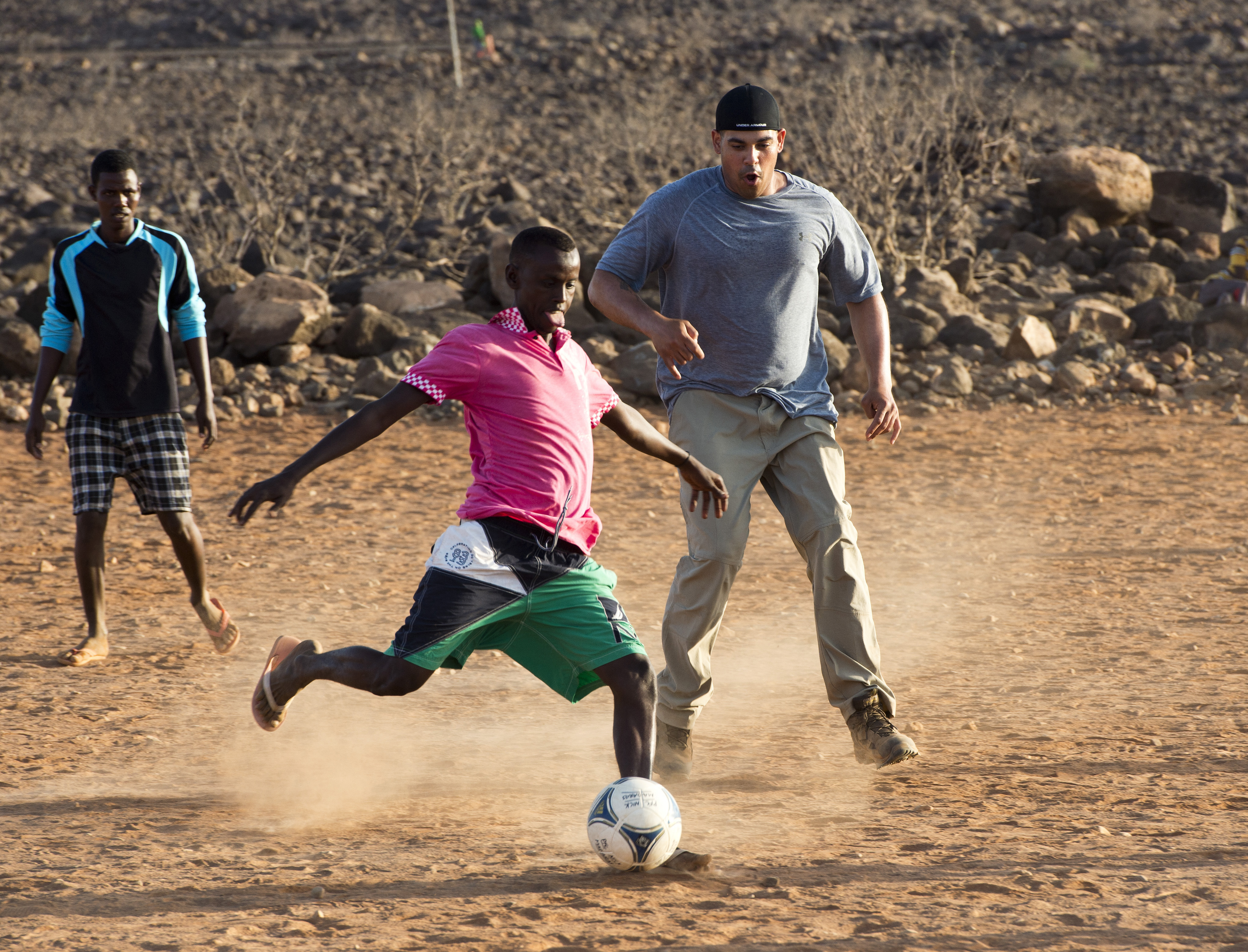 A Chebelley Village soccer player readies a kick as a defender for the Combined Joint Task Force-Horn of Africa team rushes him during the Chebelley Village Game Night soccer match at Chebelley Village, Djibouti, April 29, 2015.  The U.S. Army's 404th Civil Affairs Battalion hosts the monthly soccer match to build and grow the relationship between Chebelley Village and camp. (U.S. Air Force photo by Staff Sgt. Nathan Maysonet)