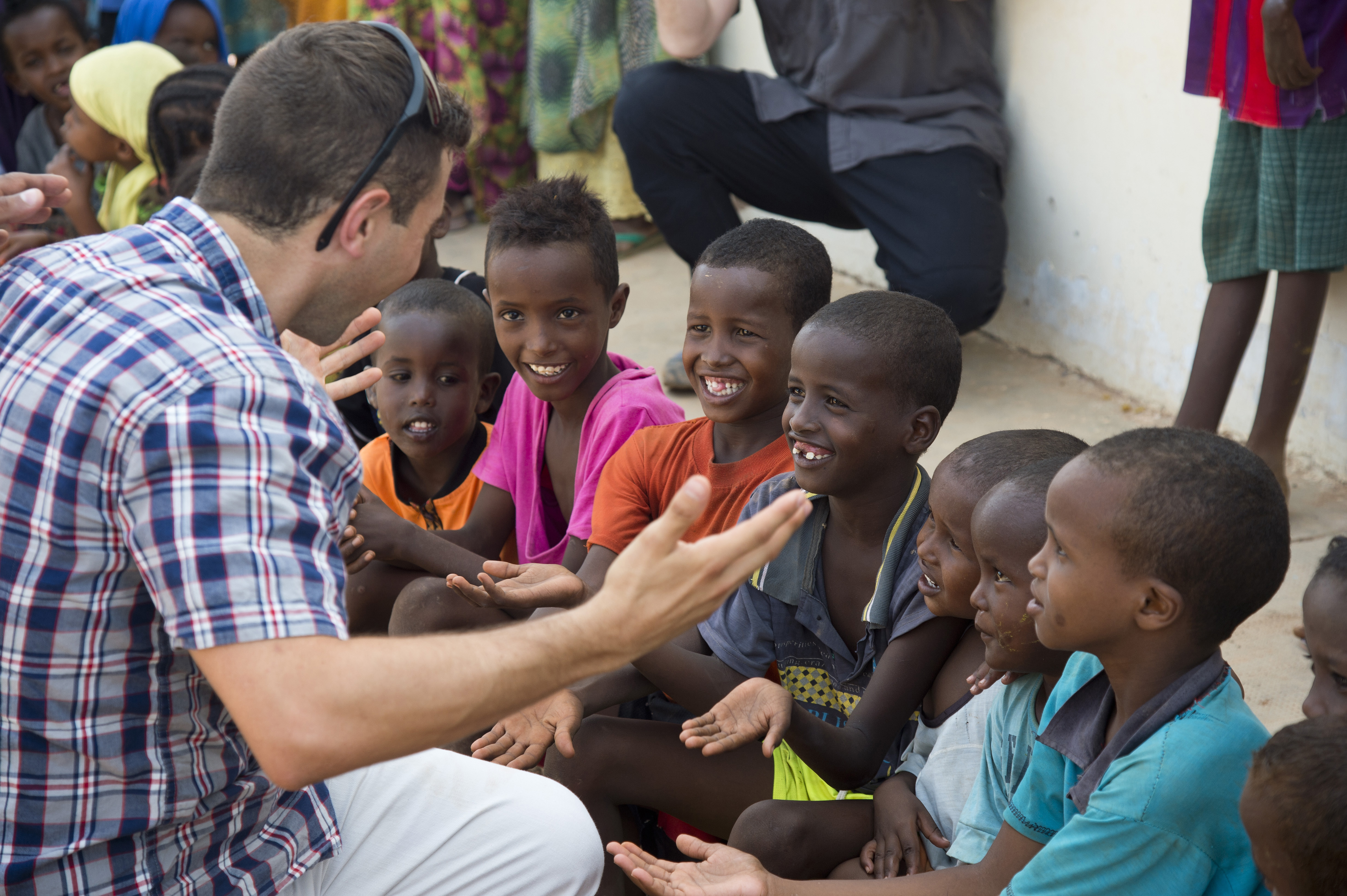 "Capt. Michael Silva, 404th Civil Affairs Battalion dentist, entertains a group of children at Chebelley Village, Djibouti, May 21, 2015. Silva was one of several volunteers from Combined Joint Task Force-Horn of Africa who helped deliver more than 40 donated soccer balls from the ""Kick for Nick"" charity to the village. (U.S. Air Force photo by Staff Sgt. Nathan Maysonet)"