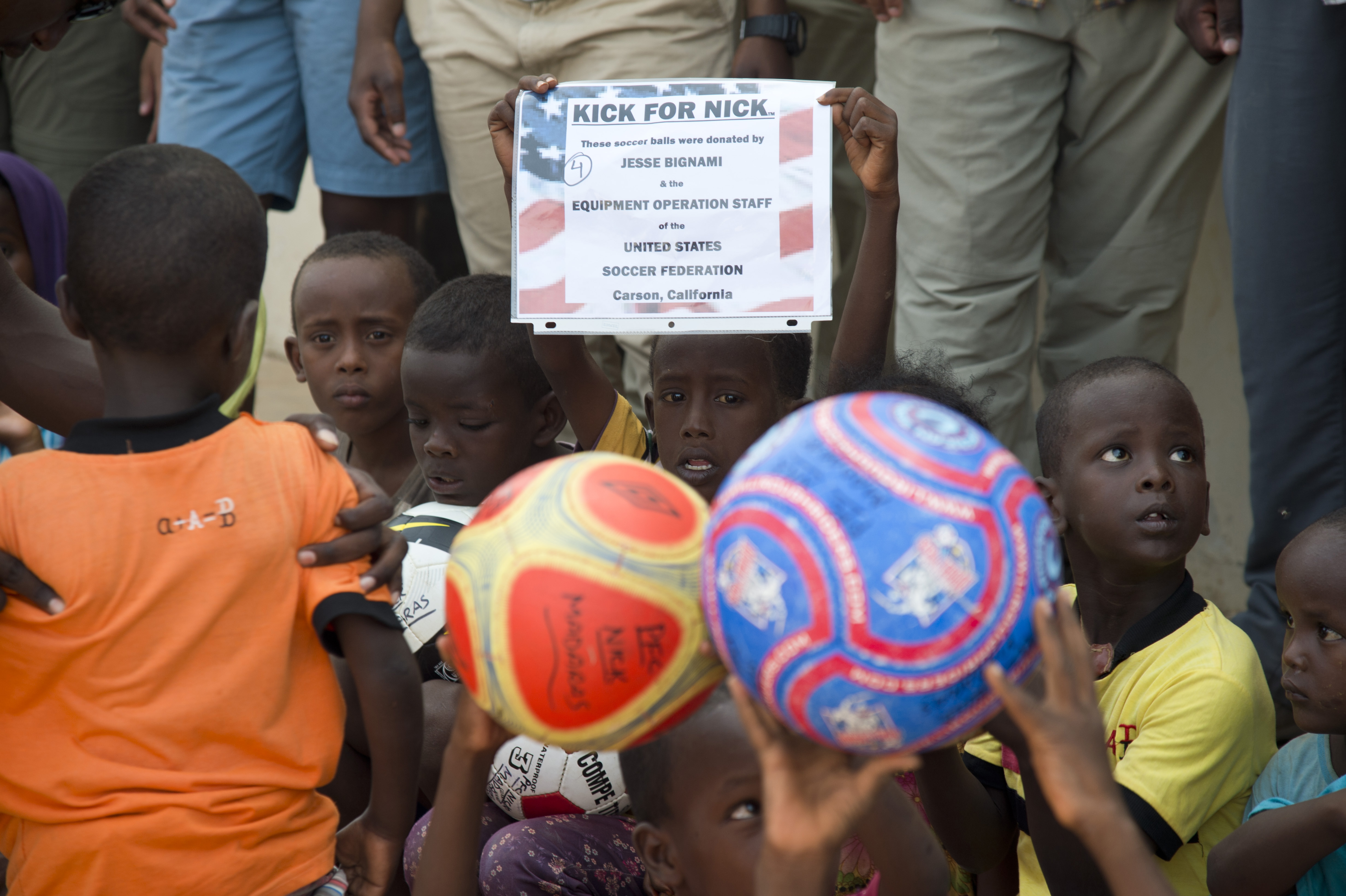 "A child holds a sign with the name of a donator who contributed to the ""kick for Nick"" charity, at Chebelley Village, Djibouti, May 21, 2015. Contributions to the charity, setup in honor of a fallen U.S. Army soldier who loved soccer, have led to thousands of soccer balls being distributed to children worldwide. (U.S. Air Force photo by Staff Sgt. Nathan Maysonet)"