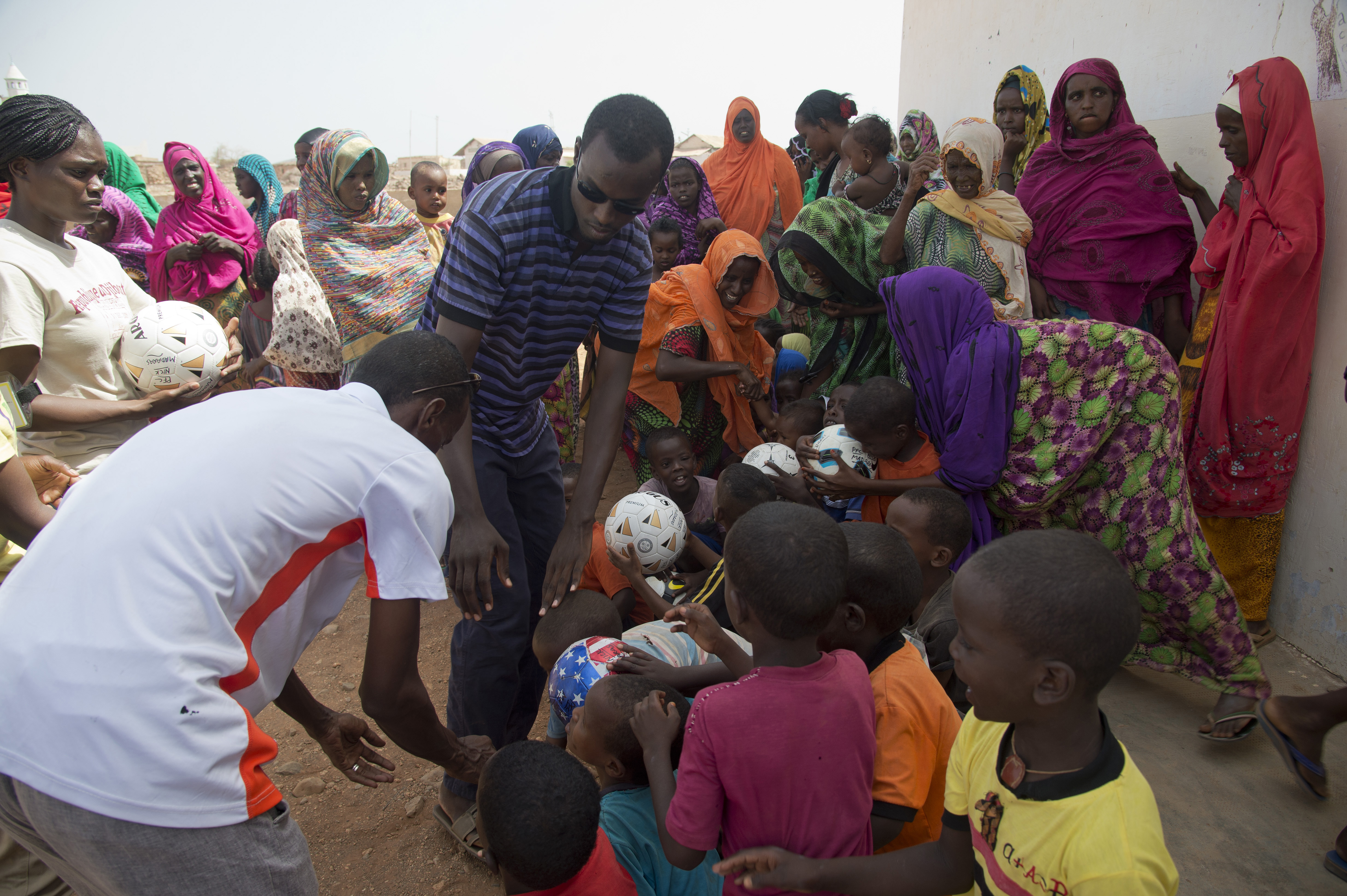 "Volunteers from Combined Joint Task Force-Horn of Africa and local villagers distribute soccer balls to the children of Chebelley Village, Djibouti, May 21, 2015. More than 40 soccer balls were given to the U.S. Army's 404th Civil Affairs Battalion (Airborne), by the ""Kick for Nick"" charity to distribute to the local children. (U.S. Air Force photo by Staff Sgt. Nathan Maysonet)"