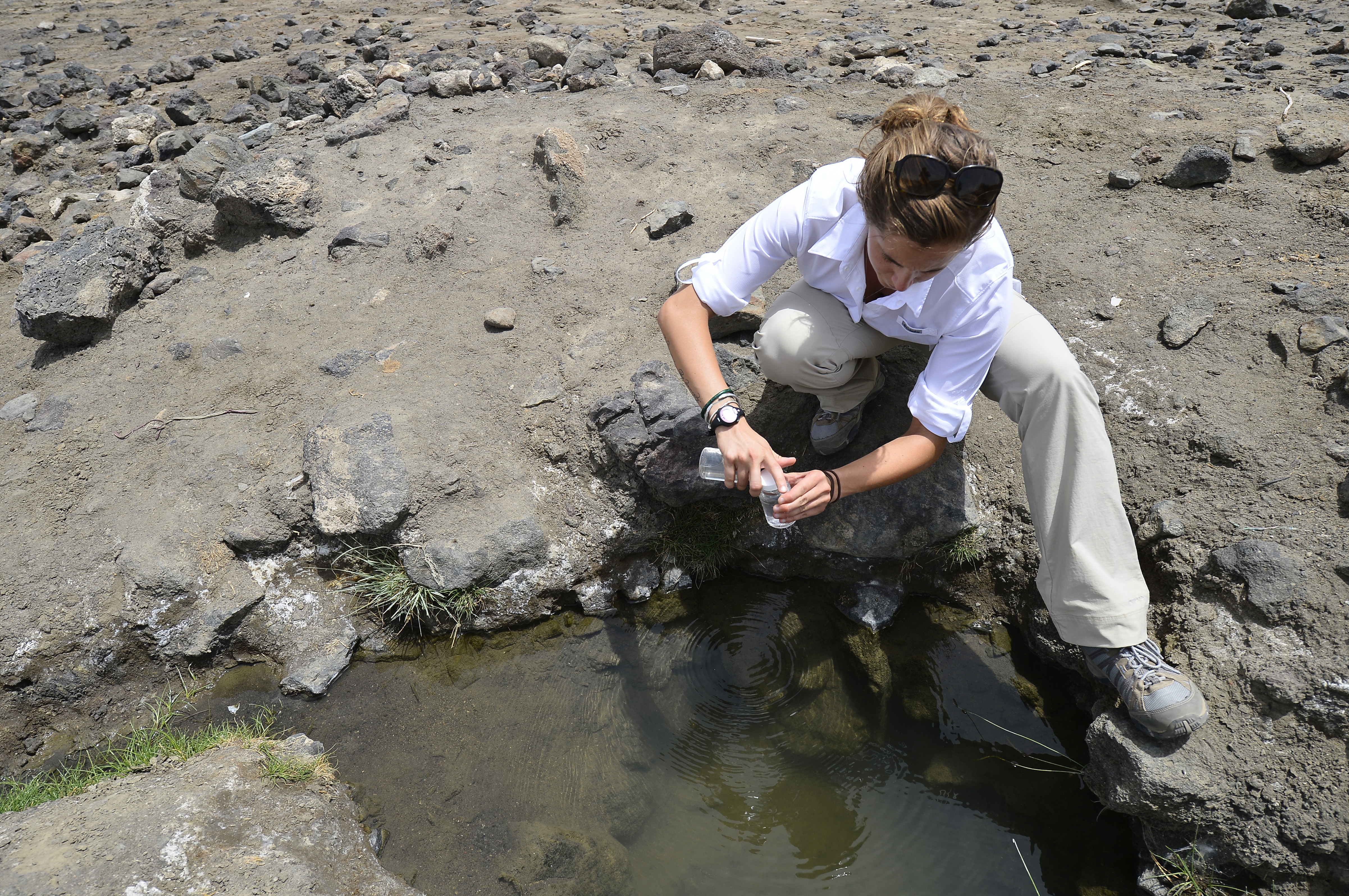 U.S. Army Spc. Caitlyn Lacomb, 404th Civil Affairs Battalion, collects a water sample in a creek near the arid Lac Abbé in Djibouti, May 20, 2015. The team assigned to Combined Joint Task Force- Horn of Africa, traveled approximately 100 miles to gather water samples and learn about the biology of the lake, along with it's utility to the nearby village. While there, the elders said it has not rained in two years, causing a drought and increasing malnourishment amongst the population. (U.S. Air Force photo by Senior Airman Nesha Humes)