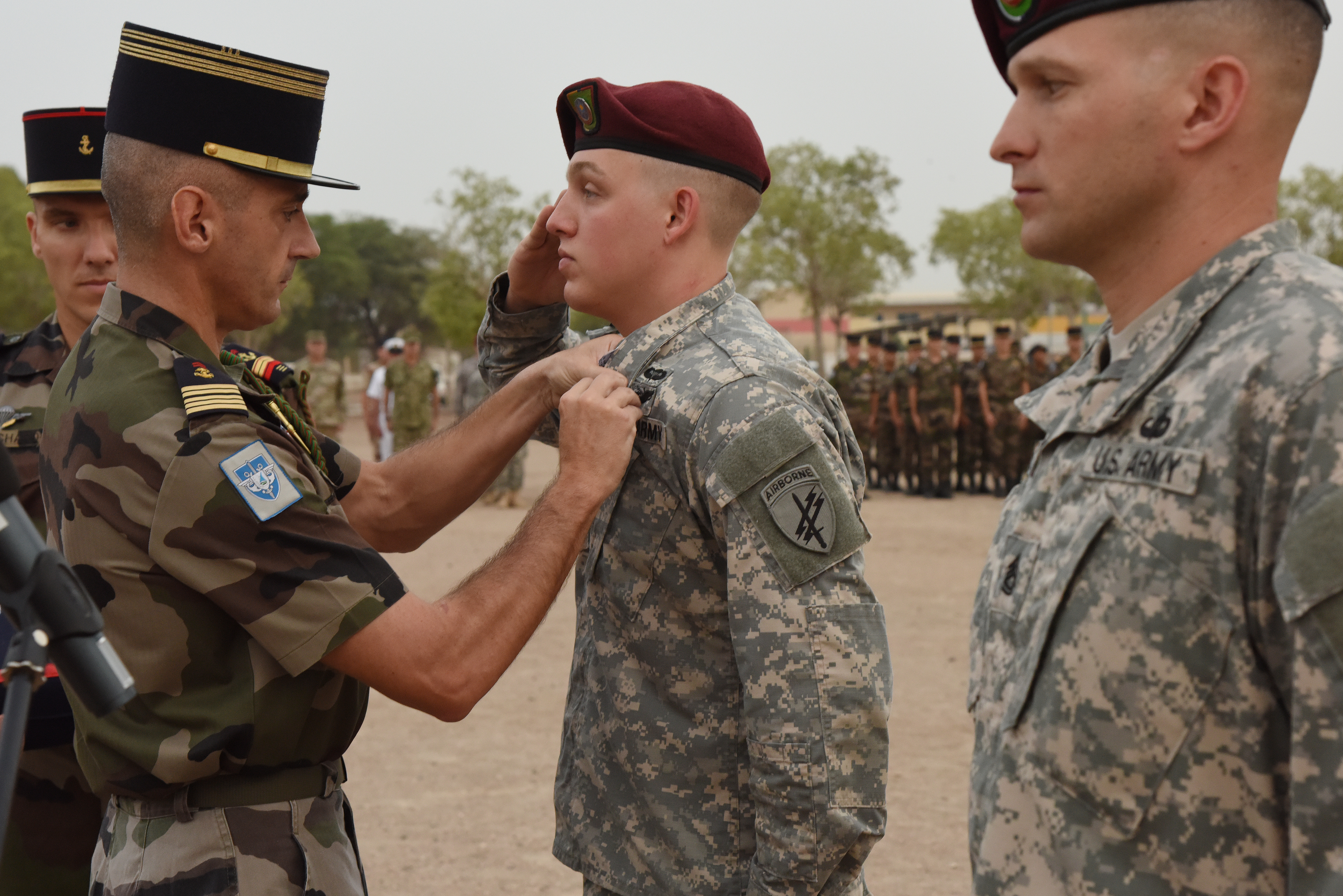 French Marine Col. Jean-Bruno Despouys, 5th Marines commanding officer, pins a National Defense Medal on U.S. Army Sgt. Robert Hames during an award ceremony at a Naval base in Djibouti, June 11, 2015, due to his life-saving medical care to a French service member during a catastrophic motor vehicle accident in February.  (U.S. Air Force photo by Staff Sgt. Maria Bowman)
