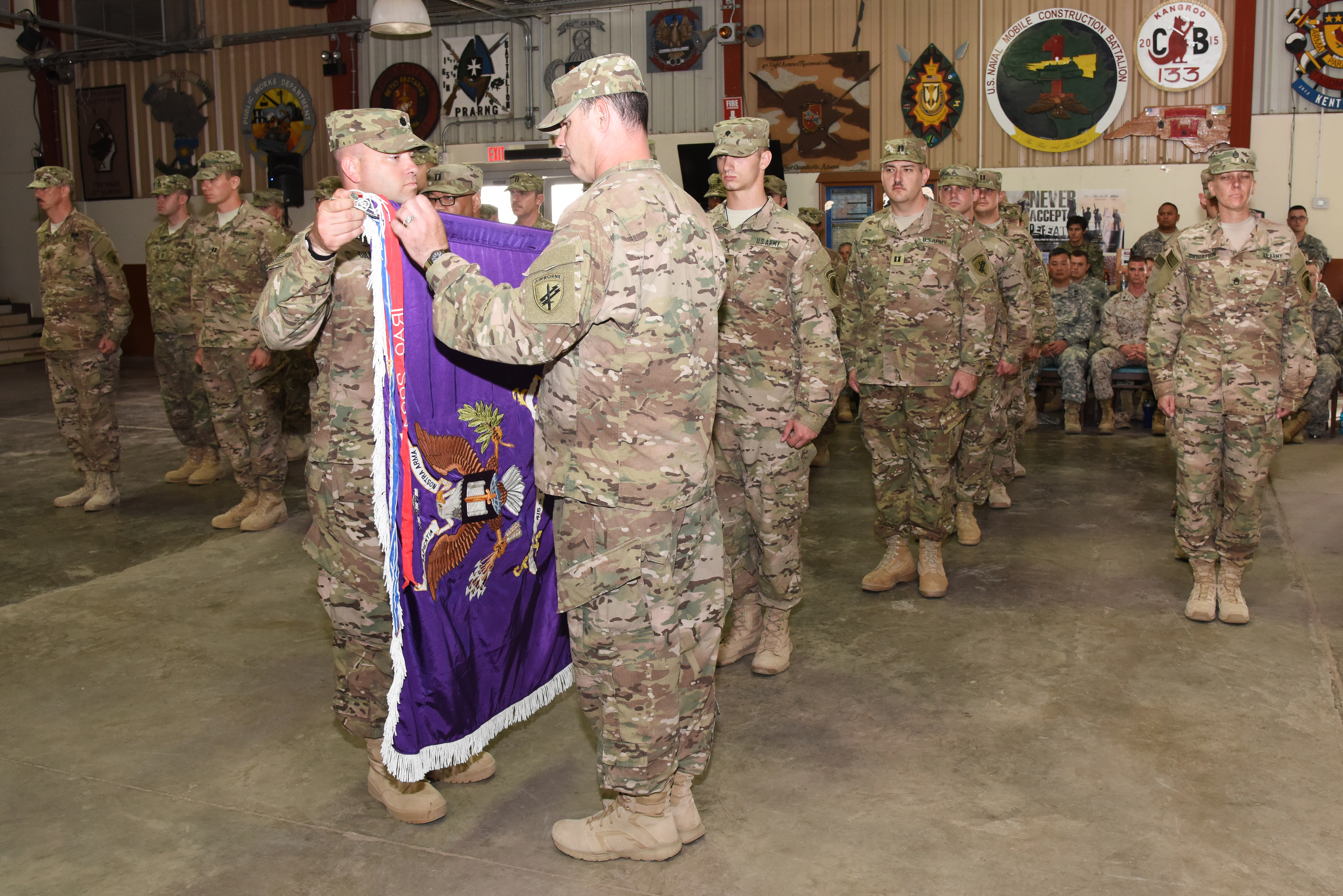 U.S. Army Lt. Col. Gerry Dolan, 415th Civil Affairs Battalion commander, unrolls his unit flag at a transfer of authority ceremony June 22, 2015 at Camp Lemonnier, Djibouti.  The uncasing of the battalion colors signifies the company's arrival from Kalamazoo, Mich., and its preparedness to assume its role within the Combined Joint Task Force-Horn of Africa. (U.S. Air Force photo by Staff Sgt. Maria Bowman)