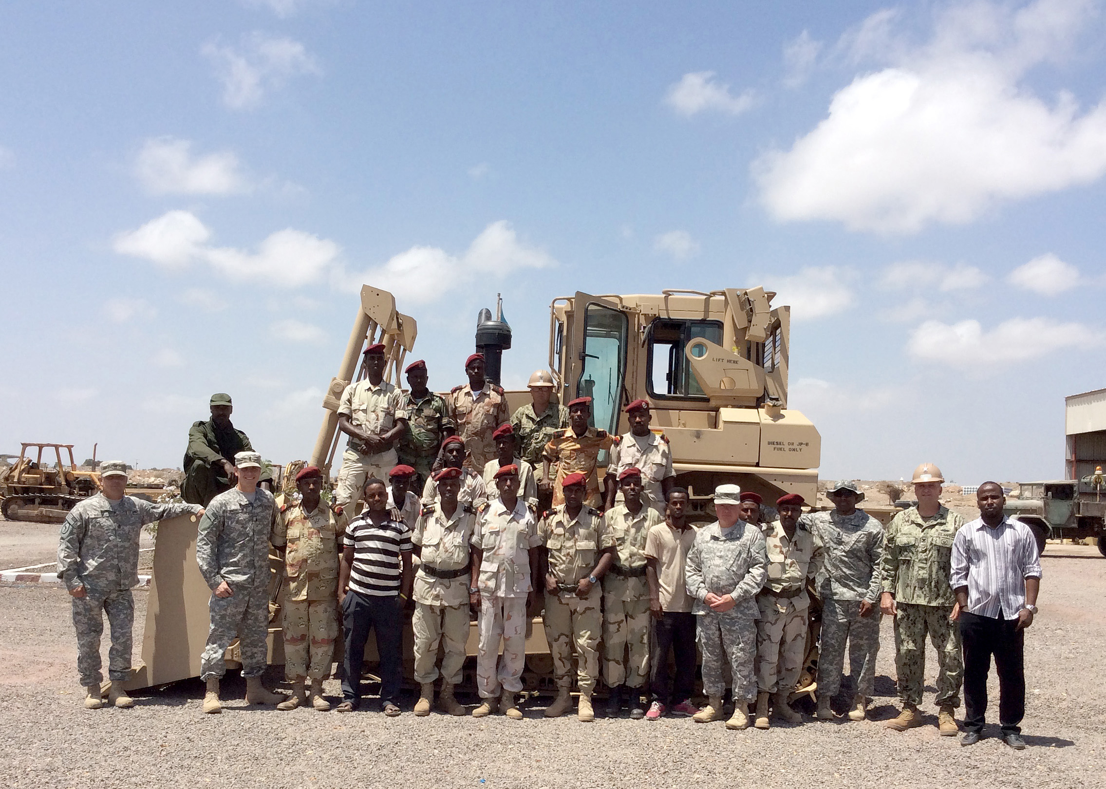 Camp Cheik Osman, Djibouti (Mar. 24, 2015) – U.S. Navy Seabees of Naval Mobile Construction Battalion (NMCB 14) pose with members of U.S. Army 47th Transportation Company and members of Forces Armee Djiboutienne (FAD) Construction Engineers in front of a D7 dozer that is now operational after the team assembled the blade and attachments. Naval Mobile Construction Battalion-14 Detachment HOA is assigned to Camp Lemonnier in support of Combined Joint Task Force–Horn of Africa. (U.S. Navy photo by Petty Officer 2nd Class Fredrick Garver)