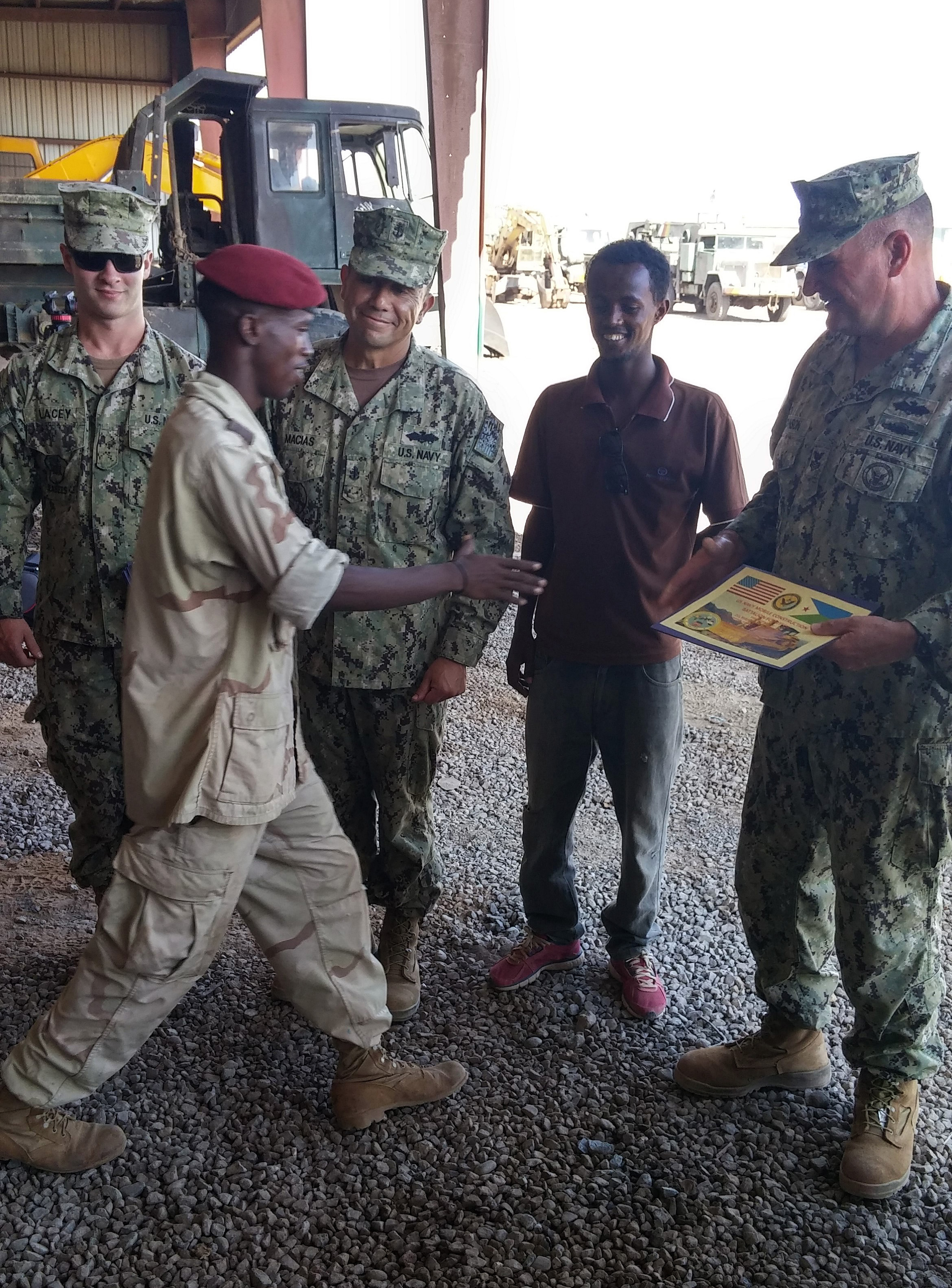 Camp Lemonnier, Djibouti (May 12, 2015) U.S. Navy Chief Petty Officer Gerardo Macias, builder, U.S. Navy Petty Officer 1st Class Douglas Johnson, construction mechanic Naval Mobile Construction Battalion (NMCB) 14 and Constructionman Austin Lacey, construction mechanic NMCB 11 present a Certificate of Recognition for completion of Equipment Operator and Maintenance training to a Djiboutian Army Equipment Operator during an awards ceremony following a U.S. Army-led training evolution. NMCB-14 Detachment HOA is assigned to Camp Lemonnier in support of Combined Joint Task Force – Horn of Africa. (U.S. Navy photo by Chief Petty Officer Ellery Sayre)