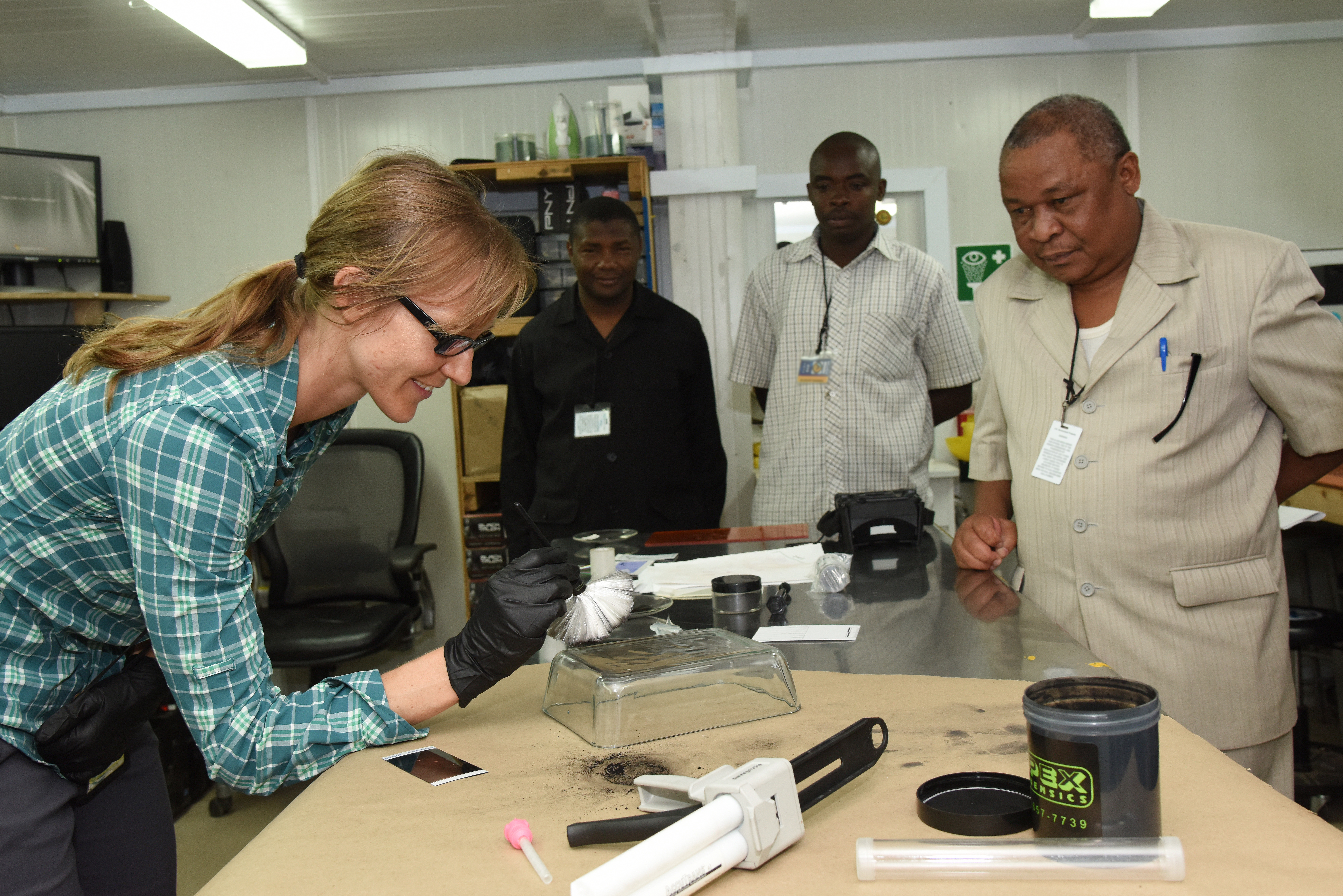 A Joint Theater Forensic Analysis Center certified latent print examiner, instructs Tanzanian Defense Force service members on how to dust for fingerprints using black powder at Camp Lemonnier, Djibouti, June 23, 2015.  The JTFAC offers training to U.S. and partner nation forces on cellular phone exploitation, unknown substance identification and fingerprint and latent printing.  (U.S. Air Force photo by Staff Sgt. Maria Bowman)