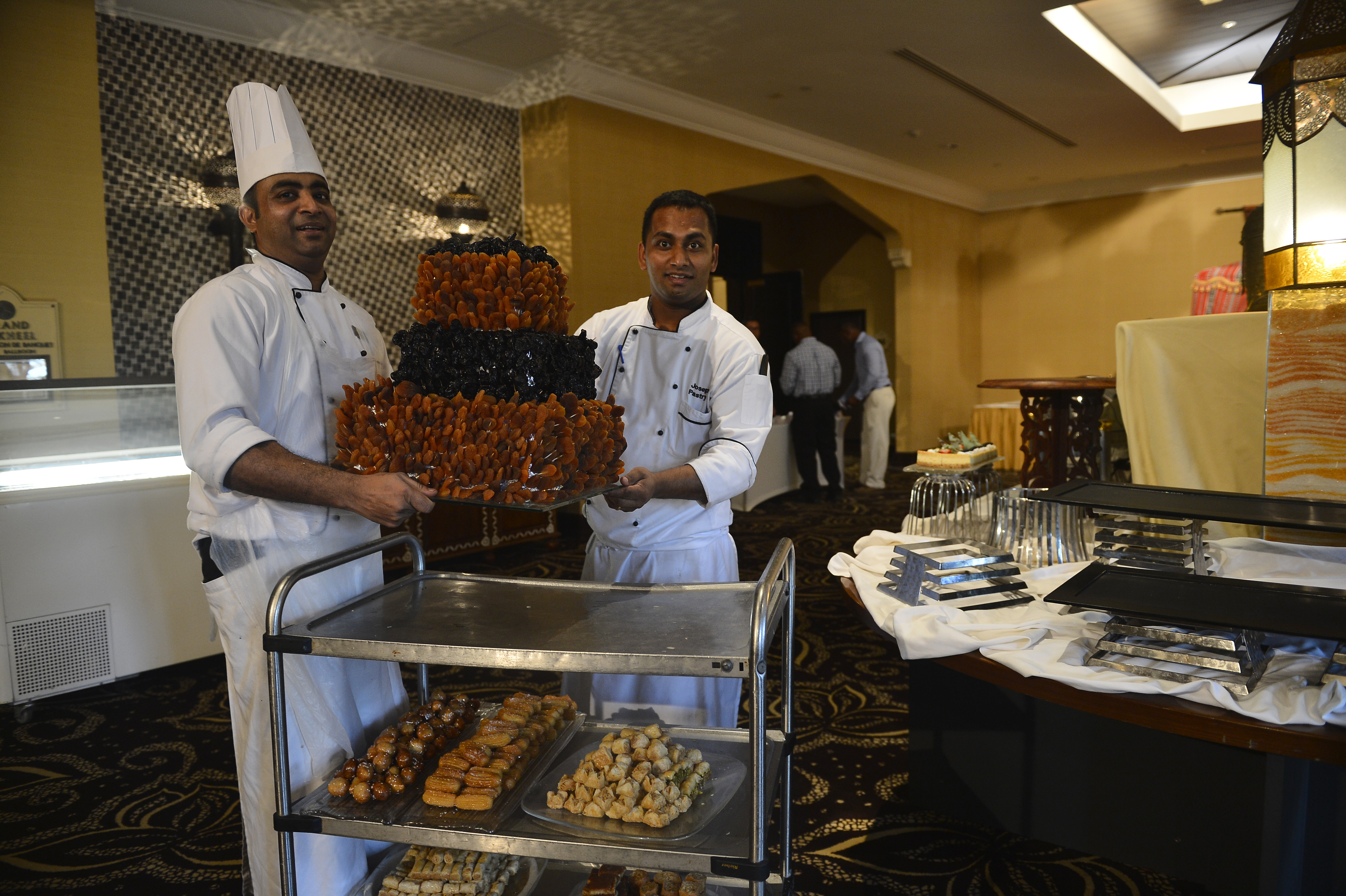From left, Joseph Joy and Ratheesh Ravai, Kempinski Hotel pastry chefs, prepare to place a cake of dates on display for Combined Joint Task Force-Horn of Africa's Iftar dinner, June 29, 2015. CJTF-HOA hosts an annual Iftar, the fast-breaking meal during the Muslim religious observance of Ramadan, to honor partner nations. Dates are traditionally eaten first to break the fast. (U.S. Air Force photo by Senior Airman Nesha Humes)