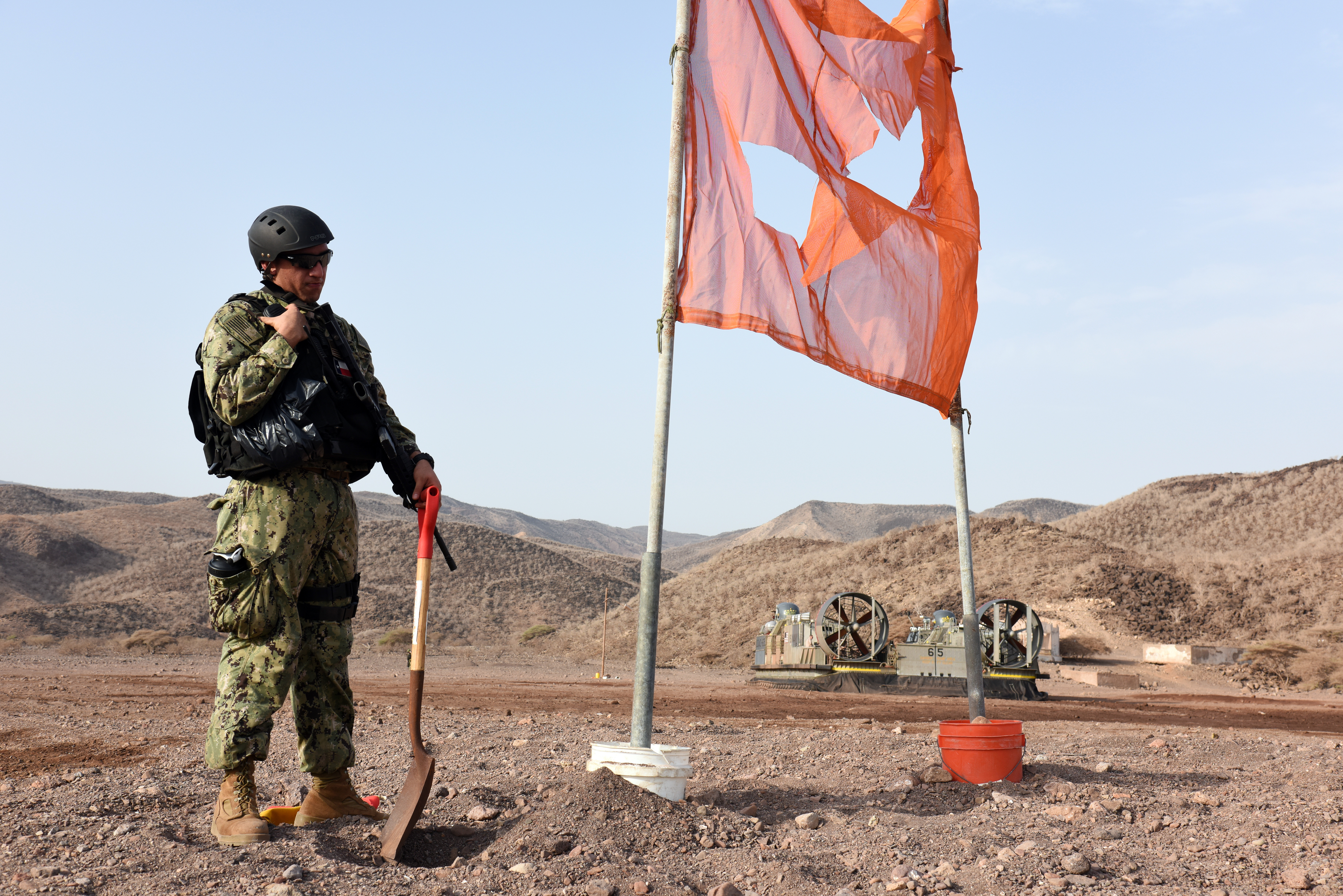 A U.S. Navy Maritime Expeditionary Security Force member completes work on a signal flag as part of sustainment training preparations for the 15th Marine Expeditionary Unit at Arta Beach, Djibouti, July 20, 2015. Signal flags are used by security forces to alert oncoming U.S. Navy Landing Craft Air Cushion (LCAC), and other landing vessels, that the beachhead is safe and secure for landing and the offloading of personnel and equipment. (U.S. Air Force photo by Staff Sgt. Nathan Maysonet)