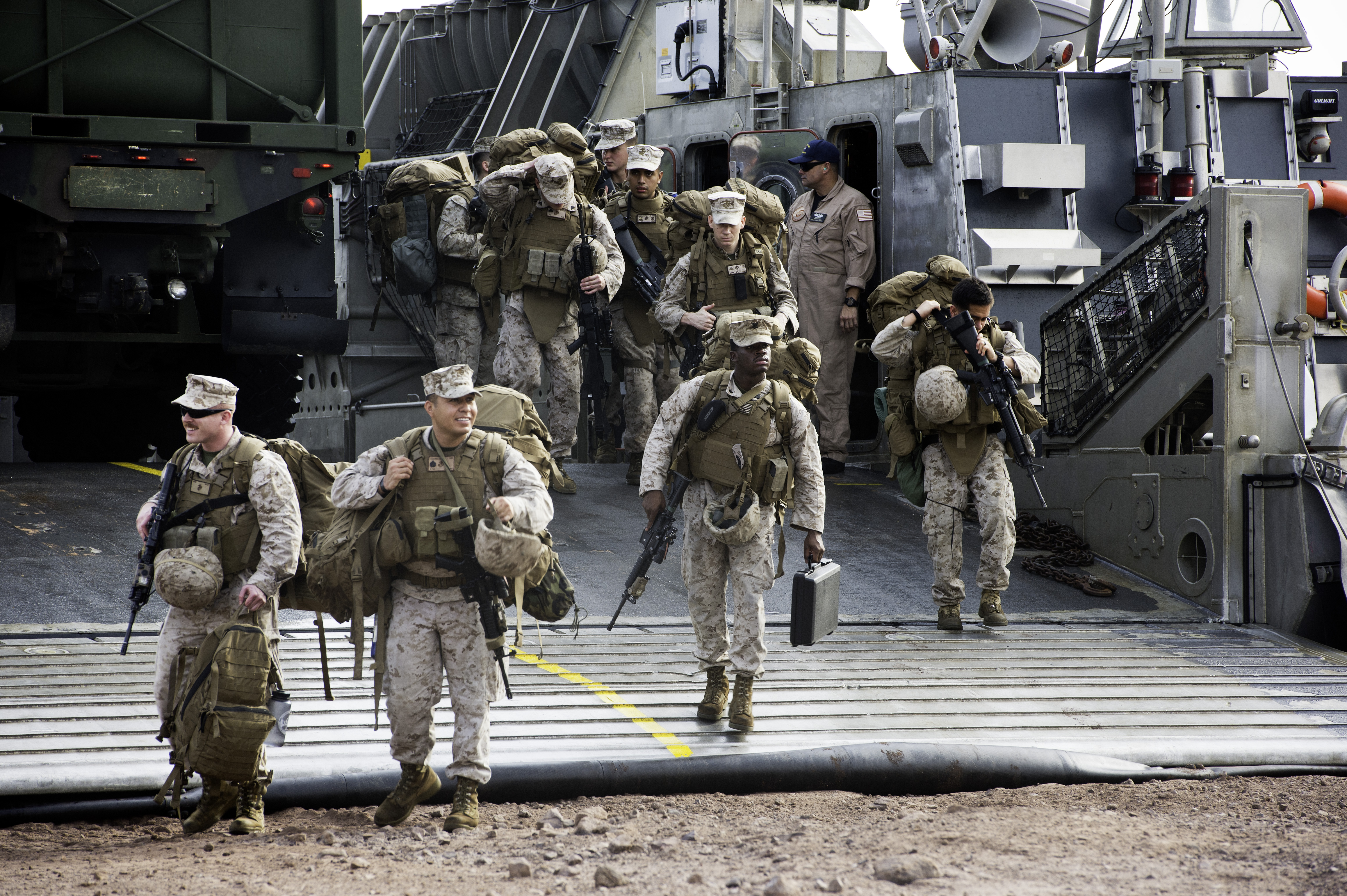 U.S. Marines from the 15th Marine Expeditionary Unit step off a U.S. Navy Landing Craft Air Cushion (LCAC) at Arta Beach, Djibouti, July 20, 2015. The Marines arrived in Djibouti from the San Antonio-class amphibious transport dock ship USS Anchorage (LPD-23) for two weeks of sustainment training which included, live fire exercises, and mounted vehicle patrols. (U.S. Air Force photo by Staff Sgt. Nathan Maysonet)