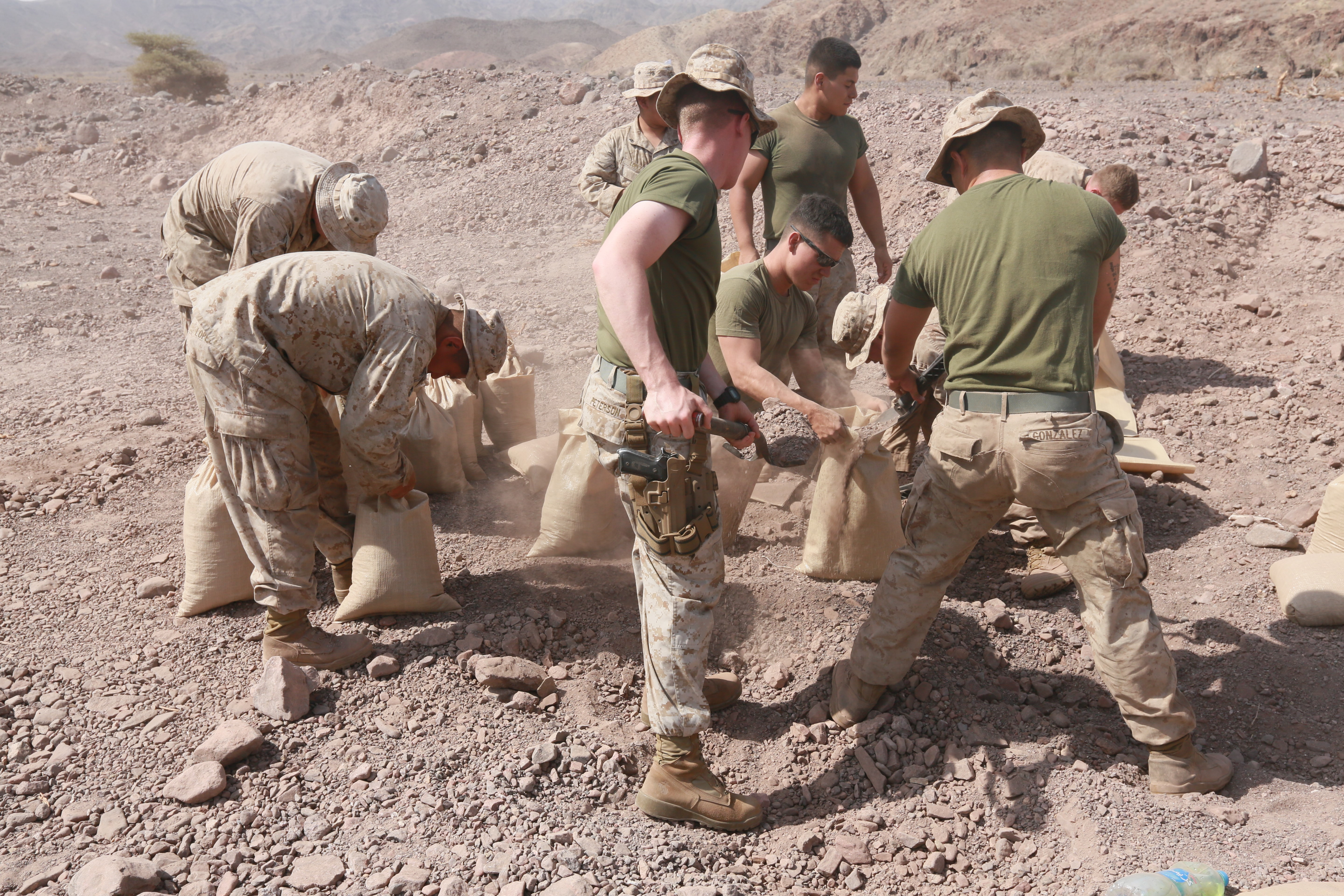ARTA BEACH, Djibouti (July 22, 2015) U.S. Marines with the 15th Marine Expeditionary Unit fill sand bags to construct an entry control point at a cantonment area ashore during sustainment training. Elements of the 15th Marine Expeditionary Unit are ashore in Djibouti for sustainment training to maintain and enhance the skills they developed during their pre-deployment training period.  The 15th MEU is currently deployed in support of maritime security operations and theater security cooperation efforts in the U.S. 5th and 6th Fleet areas of operation. (U.S. Marine Corps photo by Sgt. Steve H. Lopez/Released)