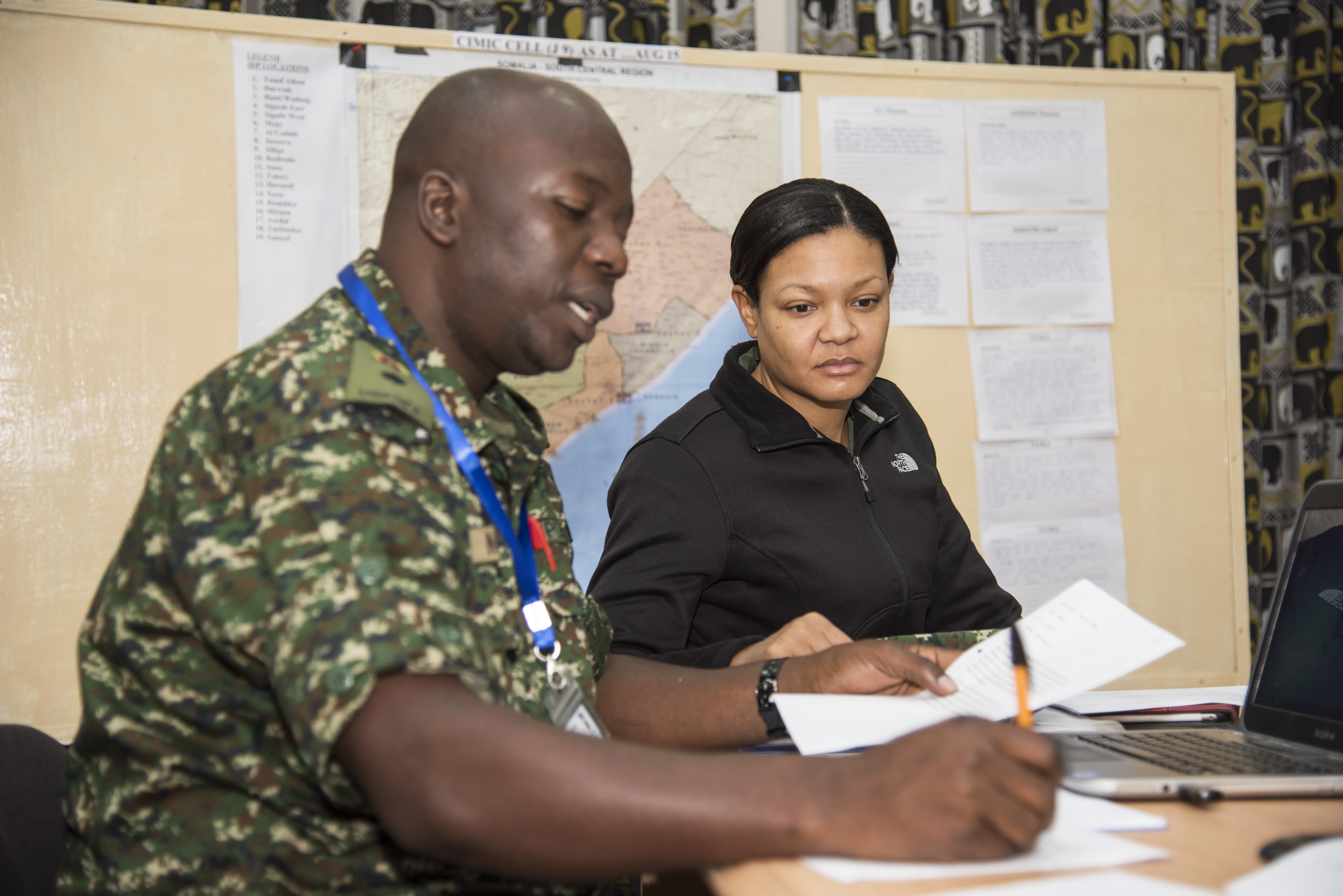 Joyce Craig, Africa Contingency Operations Training & Assistance (ACOTA) African Union Mission in Somalia (AMISOM) Force Headquarters training course instructor, right, works with a Uganda People's Defense Force officer on how to plan Civil military cooperation activities at the International Peace Support Training Center in Nairobi, Kenya, Aug. 26, 2015. The course was designed to prepare staff officers from AMISOM contributing countries for possible assignment to AMISOM Force Headquarters, and part of that training included organizing civil military operations to build support and confidence among the Somali people. (U.S. Air Force photo by Staff Sgt. Nathan Maysonet/released)