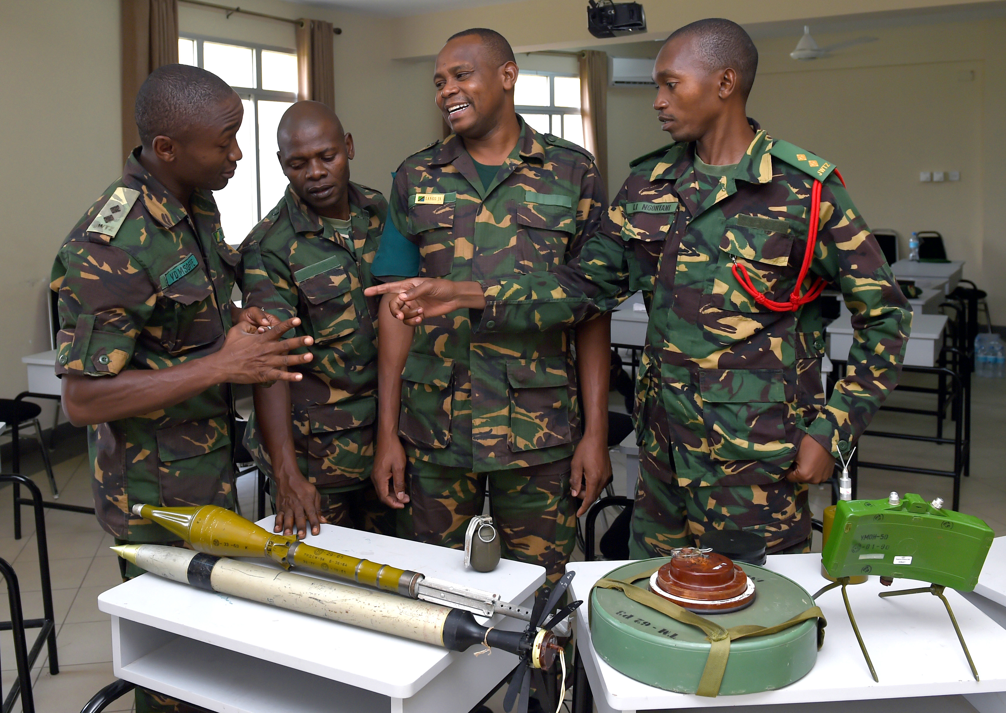 Tanzania People's Defense Force personnel look over various ordnance items during the Humanitarian Mine Action Instruction course at the Peace Keeping Training Center in Dar es Salaam, Tanzania Aug. 24, 2015. U.S. Navy Explosive Ordnance Disposal technicians, assigned to Combined Joint Task Force-Horn of Africa, instructed 22 students in order to increase partner nation's ordnance knowledge. (U.S. Air Force photo by Senior Airman Nesha Humes)
