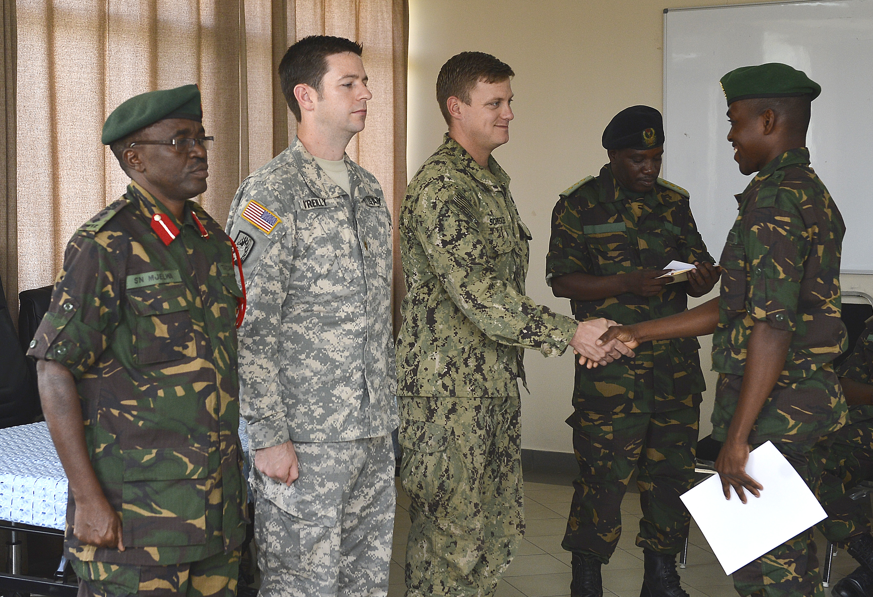 An Explosive Ordnance Disposal Technician, assigned to CJTF-HOA, congratulates Pvt.Ramadhan Badru Mwita, a Tanzania People's Defense Force ammunition technician, during the Humanitarian Mine Action course graduation at the Peace Keeping Training Center in Dar es Salaam, Tanzania Aug. 27, 2015. (U.S. Air Force photo by Senior Airman Nesha Humes)