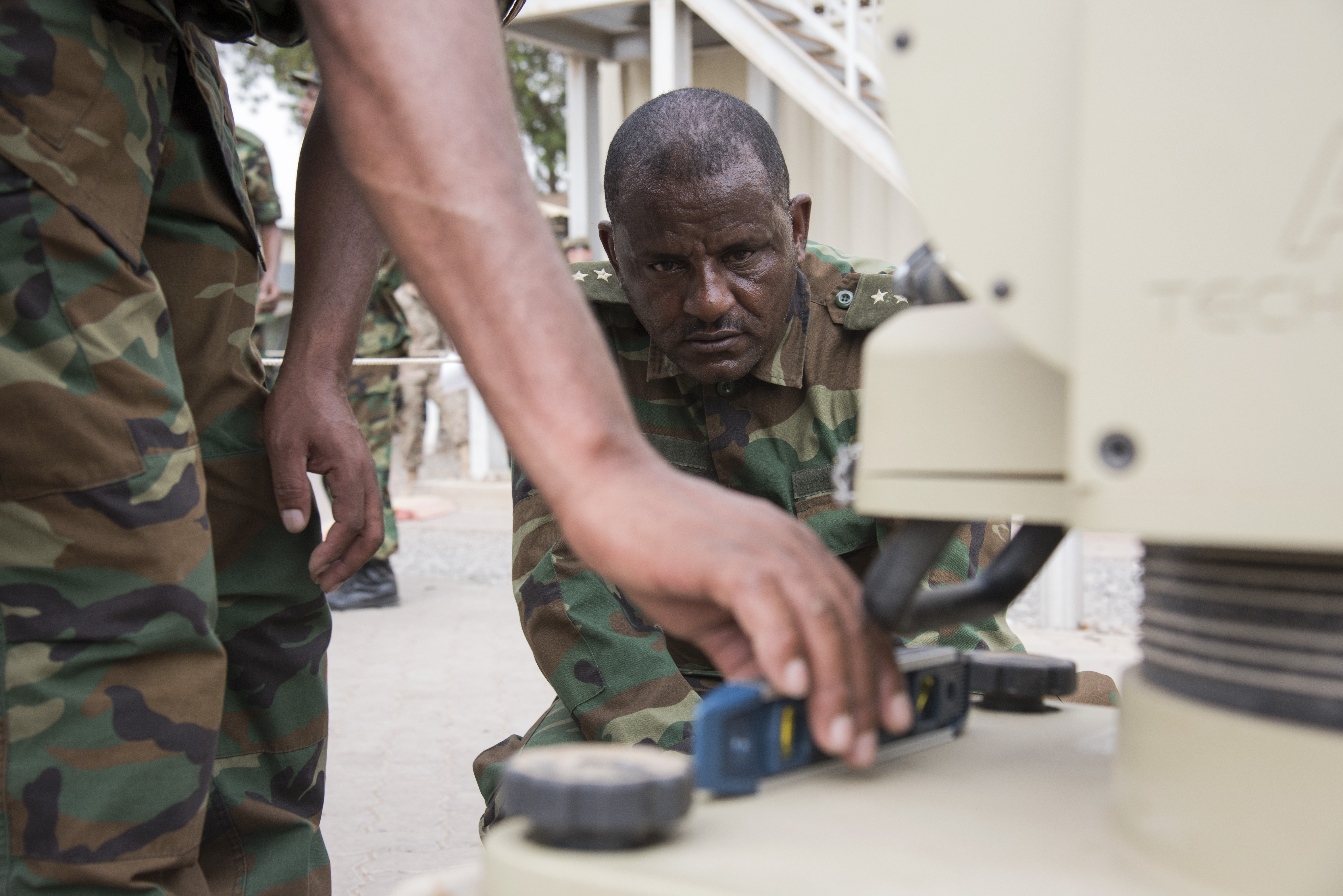 Members of the Ethiopian National Defense Force (ENDF) level the body of a U.S. Africa Command Data Sharing Network (ADSN) terminal at Camp Lemonnier, Djibouti, Aug 18, 2015. ENDF personnel were tested on how quickly they could setup and tear down the field communication system as part of a multi-week ADSN course designed to broaden communication interoperability between host nation security forces, which was hosted by communications and intelligence personnel assigned to Combined Joint Task Force-Horn of Africa. (U.S. Air Force photo by Staff Sgt. Nathan Maysonet/released)