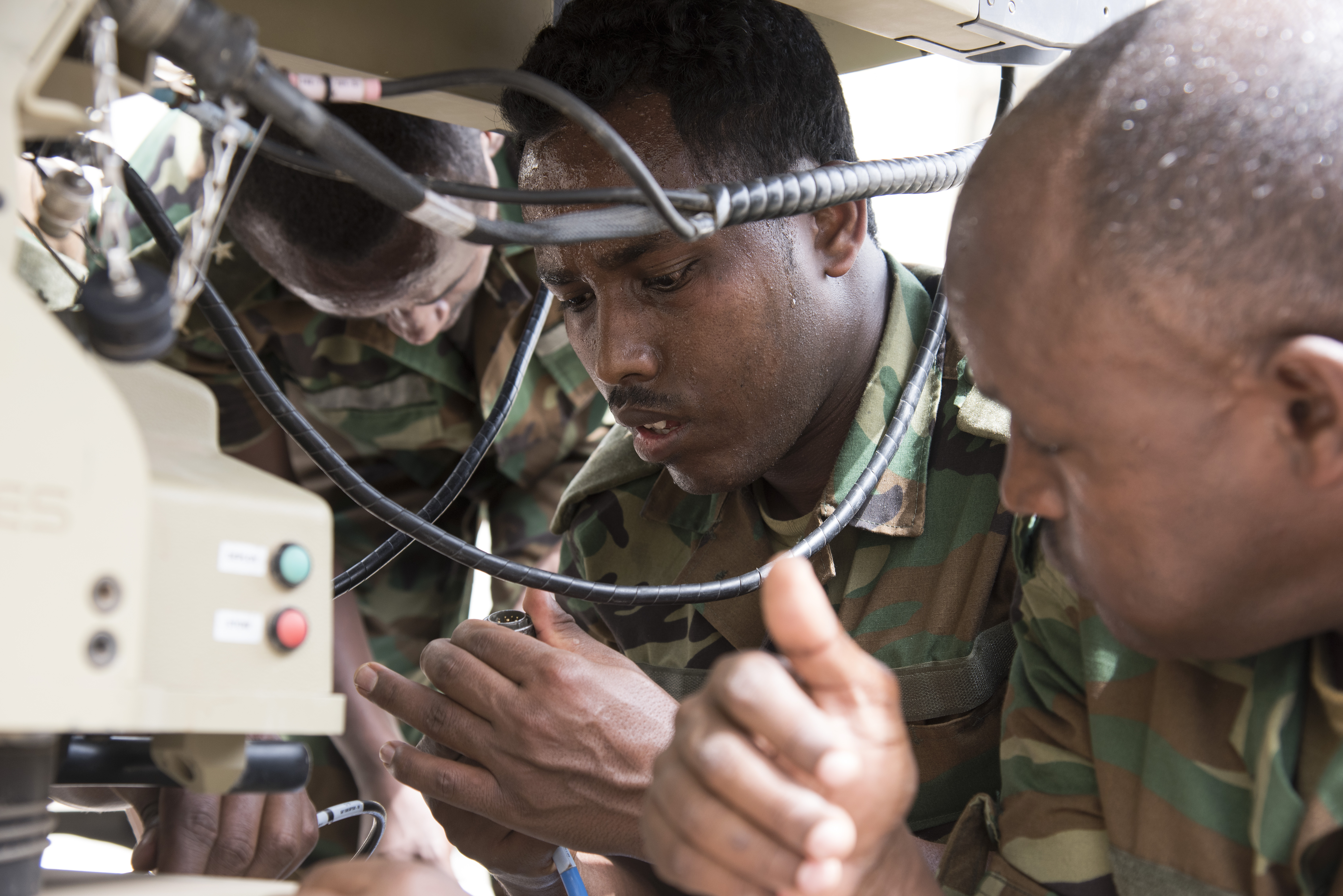 Members of the Ethiopian National Defense Force (ENDF) inspect connection cables during setup of a U.S. Africa Command Data Sharing Network (ADSN) terminal at Camp Lemonnier, Djibouti, Aug. 18, 2015. ENDF personnel were tested on how quickly they could setup and tear down the field communication system as part of a multi-week ADSN course, which was hosted by Combined Joint Task Force-Horn of Africa communications and intelligence personnel, and was designed to broaden communication interoperability between host nation security forces. (U.S. Air Force photo by Staff Sgt. Nathan Maysonet/released)