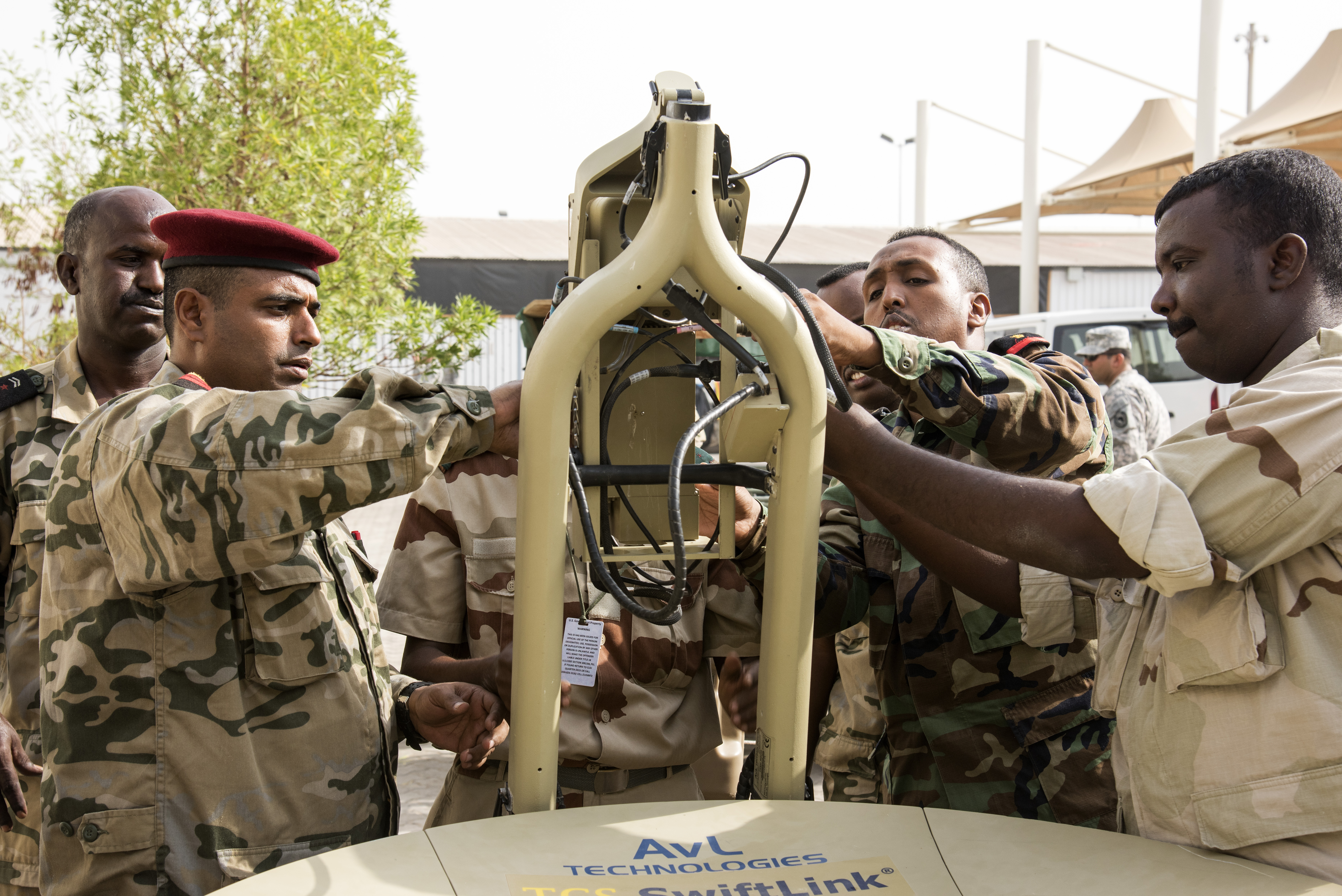 Members of the Djibouti Armed Forces (FAD) assemble the feed horn of a U.S. Africa Command Data Sharing Network (ADSN) terminal at Camp Lemonnier, Djibouti, Aug. 31, 2015. The feed horn is used to transmit a signal by using the dish to focus the signal into a narrow stream and to receive transmissions reflected by the dish. The setup and tear down of the ADSN field communication system was part of a multi-week course, which was hosted by Combined Joint Task Force-Horn of Africa communications and intelligence personnel, and was designed to broaden communication interoperability between host nation security forces. (U.S. Air Force photo by Staff Sgt. Nathan Maysonet/released)