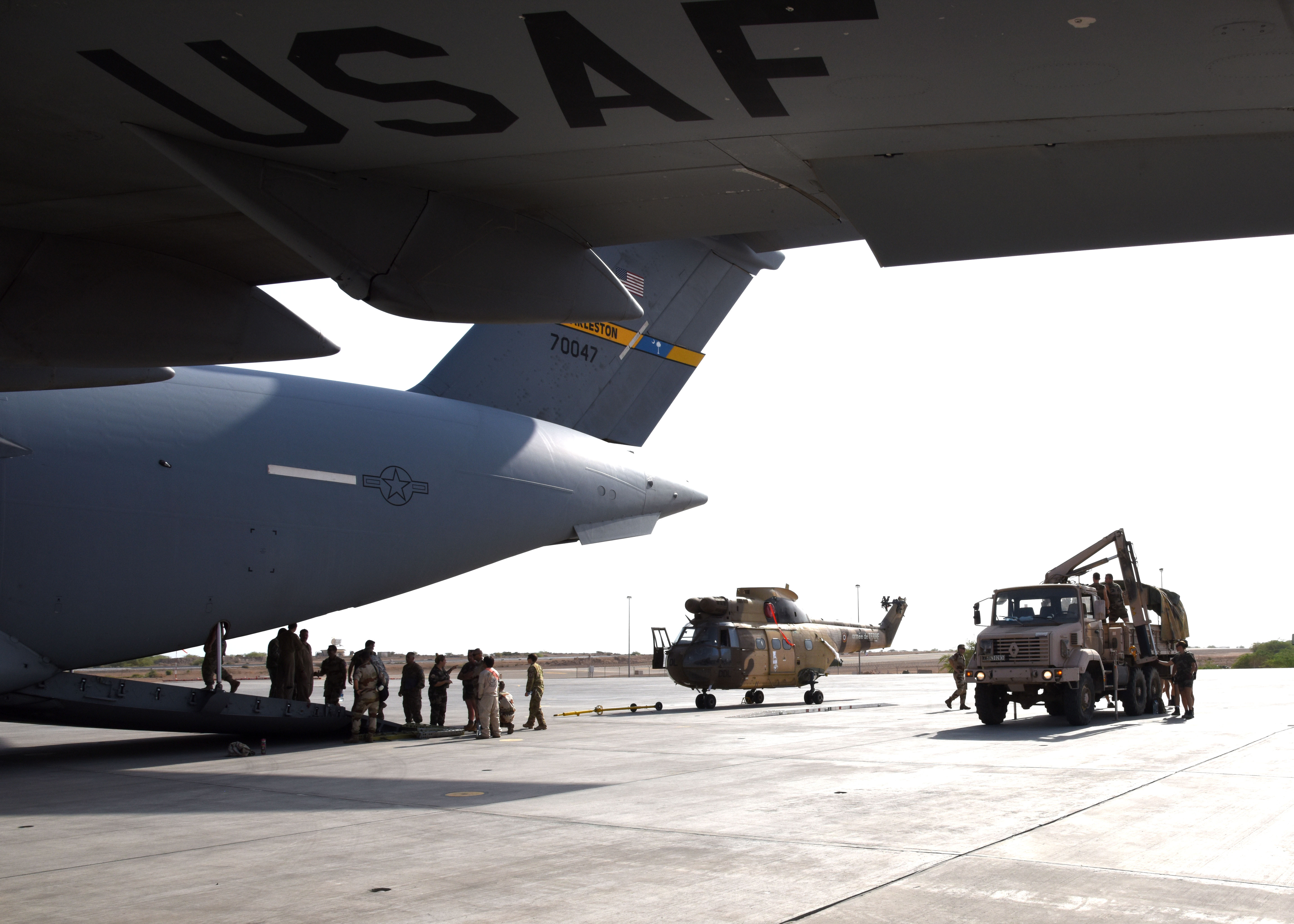 150823-N-DJ346-003 CAMP LEMONNIER, Djibouti (August 23, 2015) French and U.S. service members prepare to transport two French Puma Helicopters and associated Passengers & Cargo to N'Djamena aboard a U.S. Air Force C-17 Globemaster. The helicopters support French operations at the intersecting borders of Libya, Chad and Niger deterring weapons and drug smuggling, and jihadist regularly crossing between nations. This is the first time France has received support from U.S. Forces in Djibouti for any mission outside of East Africa. (U.S. Navy photo by Chief Mass Communication Specialist Donald W. Randall/Released)