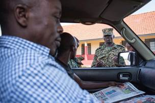 Uganda People's Defense Force (UPDF) Capt. Cox Russels Kokole, information officer, speaks with vehicle passengers during an information operations field exercise, hosted by personnel from Combined Joint Task Force-Horn of Africa, at Jinja, Uganda, recently. Attendees of the course learned how to engage persons in face-to-face communications in order to disseminate messages to inform and counter violent extremist groups. (U.S. Air Force photo by Staff Sgt. Nathan Maysonet)