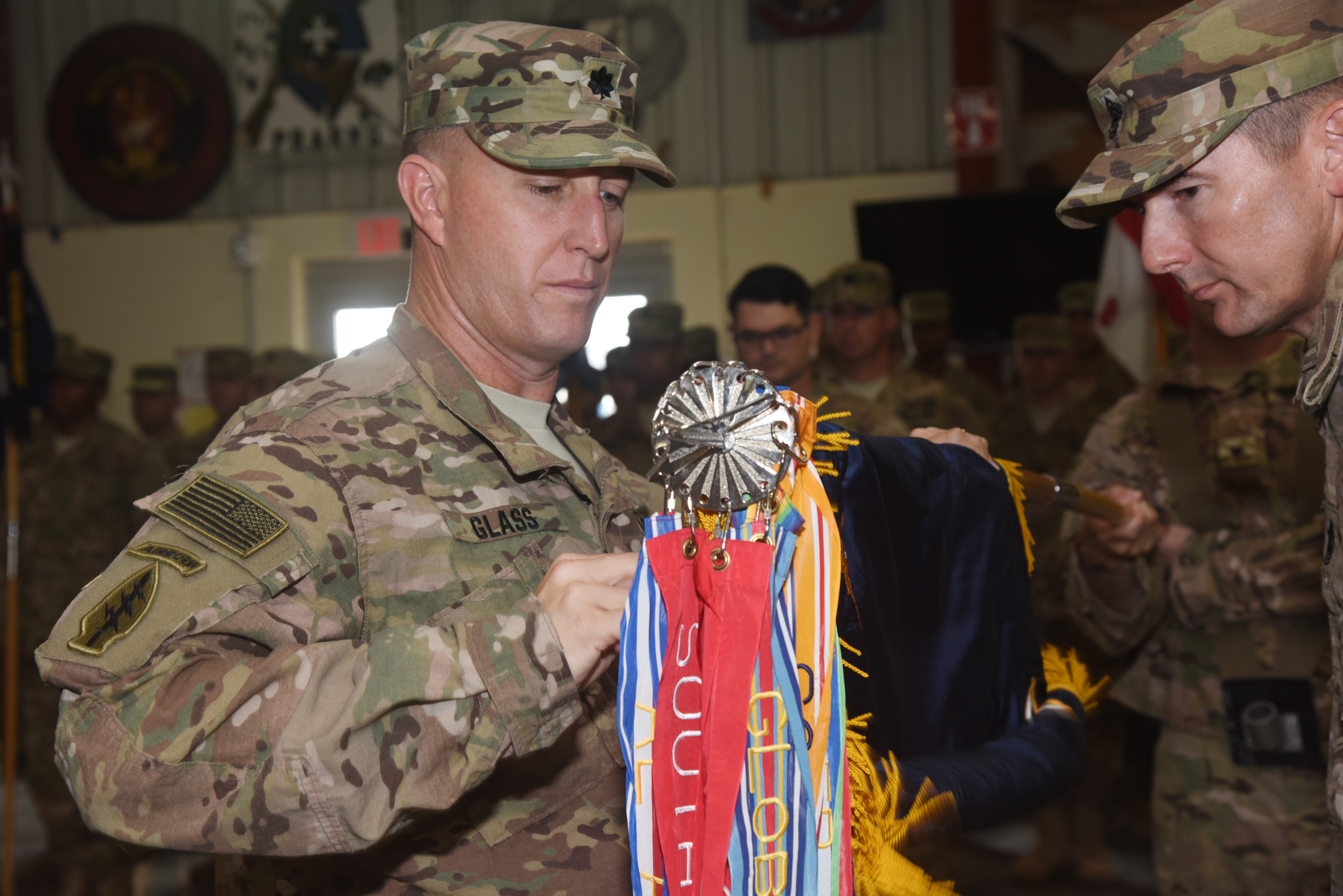 Lt. Col. Jerry Glass, 2nd Battalion, 124th Infantry Regiment commander, unrolls his unit flag at a transfer of authority ceremony Sept. 24, 2015, at Camp Lemonnier, Djibouti.  The uncasing of the regiment colors signifies the battalion's arrival from Florida, and the soldiers' preparedness to assume its role within Combined Joint Task Force-Horn of Africa.  (U.S. Air Force photo by Staff Sgt. Maria Bowman)