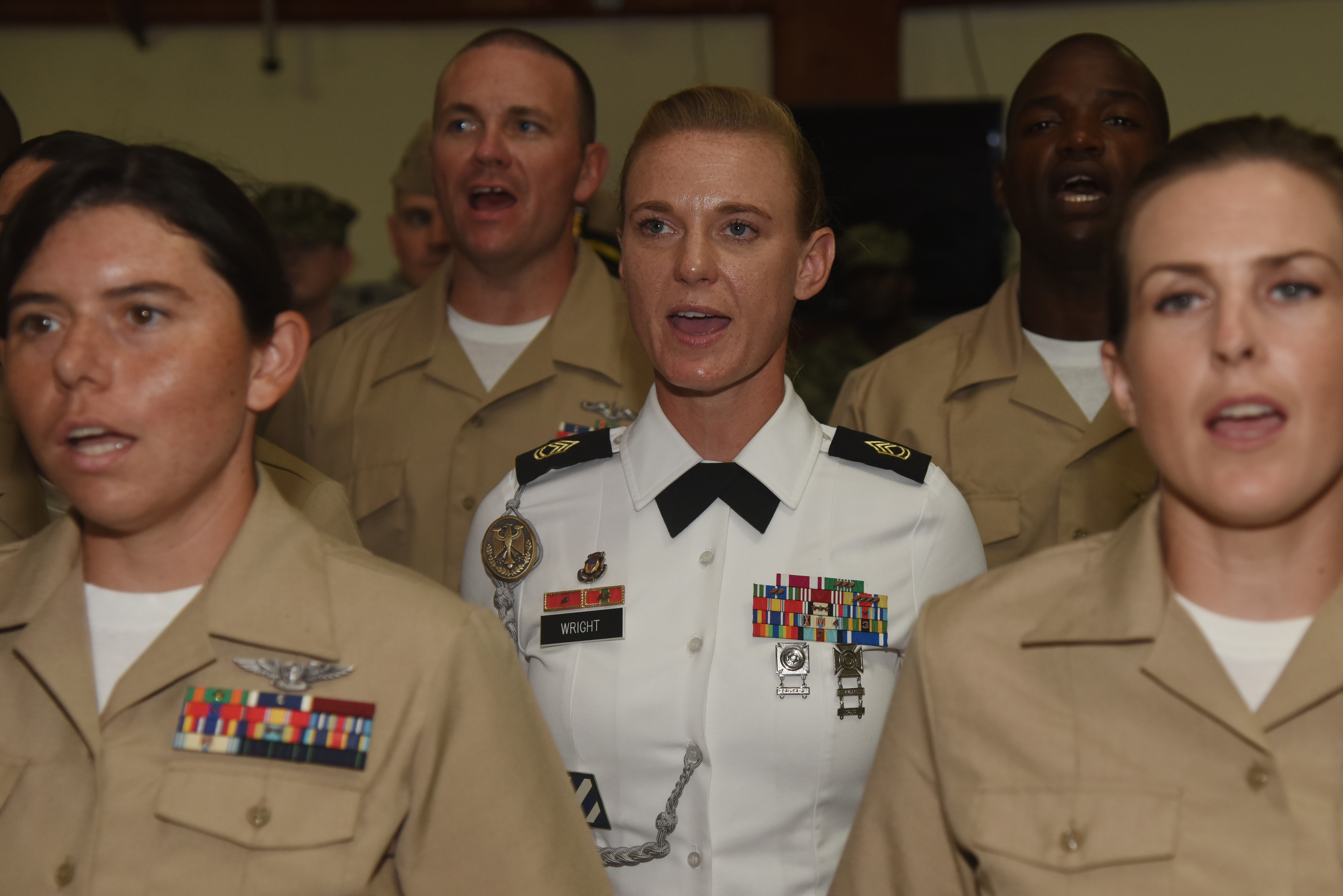 U.S. Army Sgt. 1st Class Heather Wright, Army Command Element NCO in charge, sings the Navy song, Anchors Aweigh, during a pinning ceremony at Camp Lemonnier, Djibouti, Sept. 16, 2015. Wright was the only Army soldier to attend the Navy Chief Petty Officer 365 Phase Two at the camp, which teaches leadership skills to senior noncommissioned officers.  (U.S. Air Force photo by Staff Sgt. Maria Bowman)