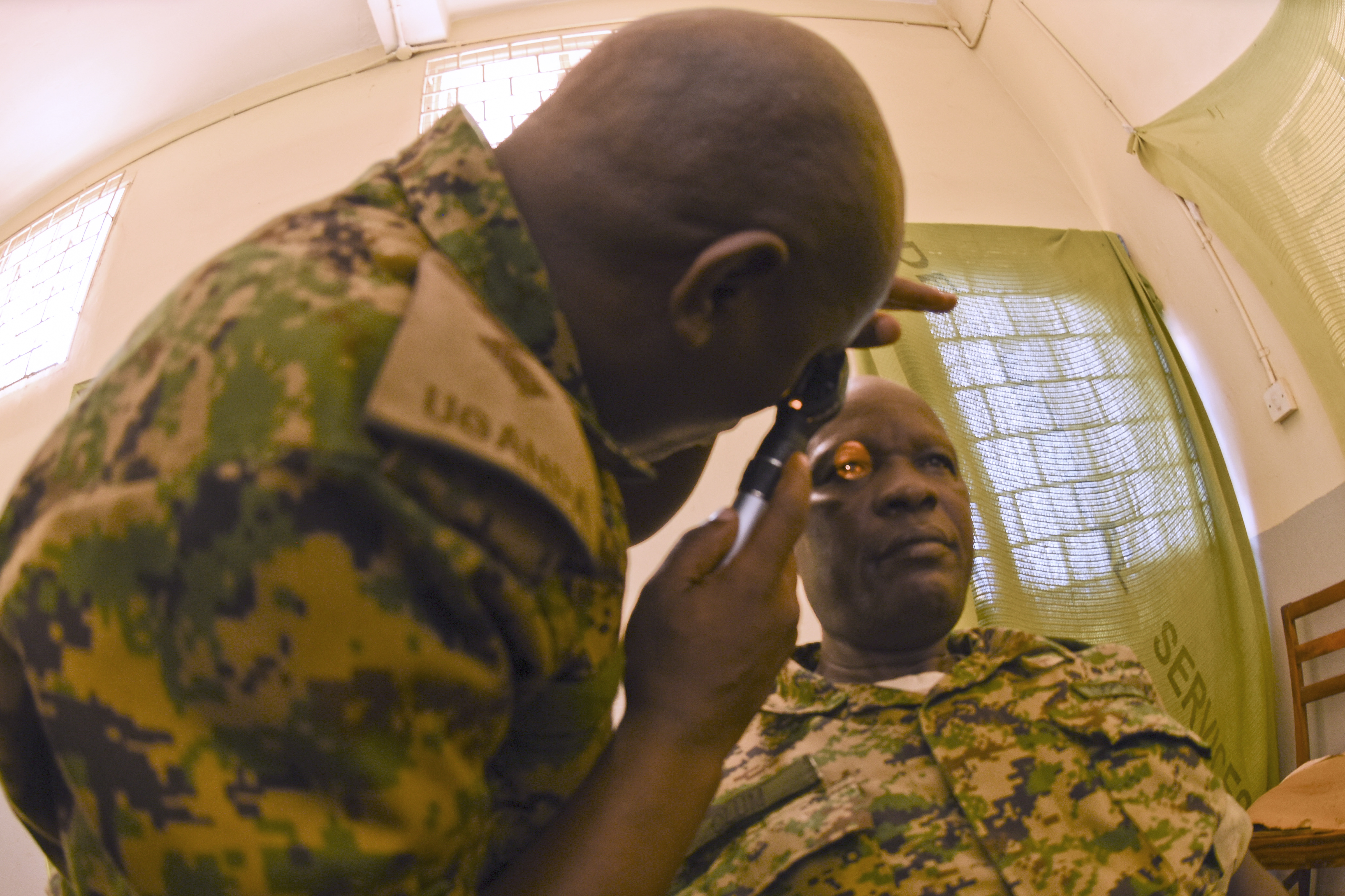 Lt. Jarvis Amagara Muhairwe, ophthalmologist, examines a UPDF soldier during MEDRETE 15-4 on September 21, 2015 in Jinja, Uganda.  This exercise focused on exchange of best practices strengthening U.S. strategic partnerships with UPDF to enhance readiness and interoperability. (U.S. Air Force photo by Master Sgt. Charlene M. Spade)