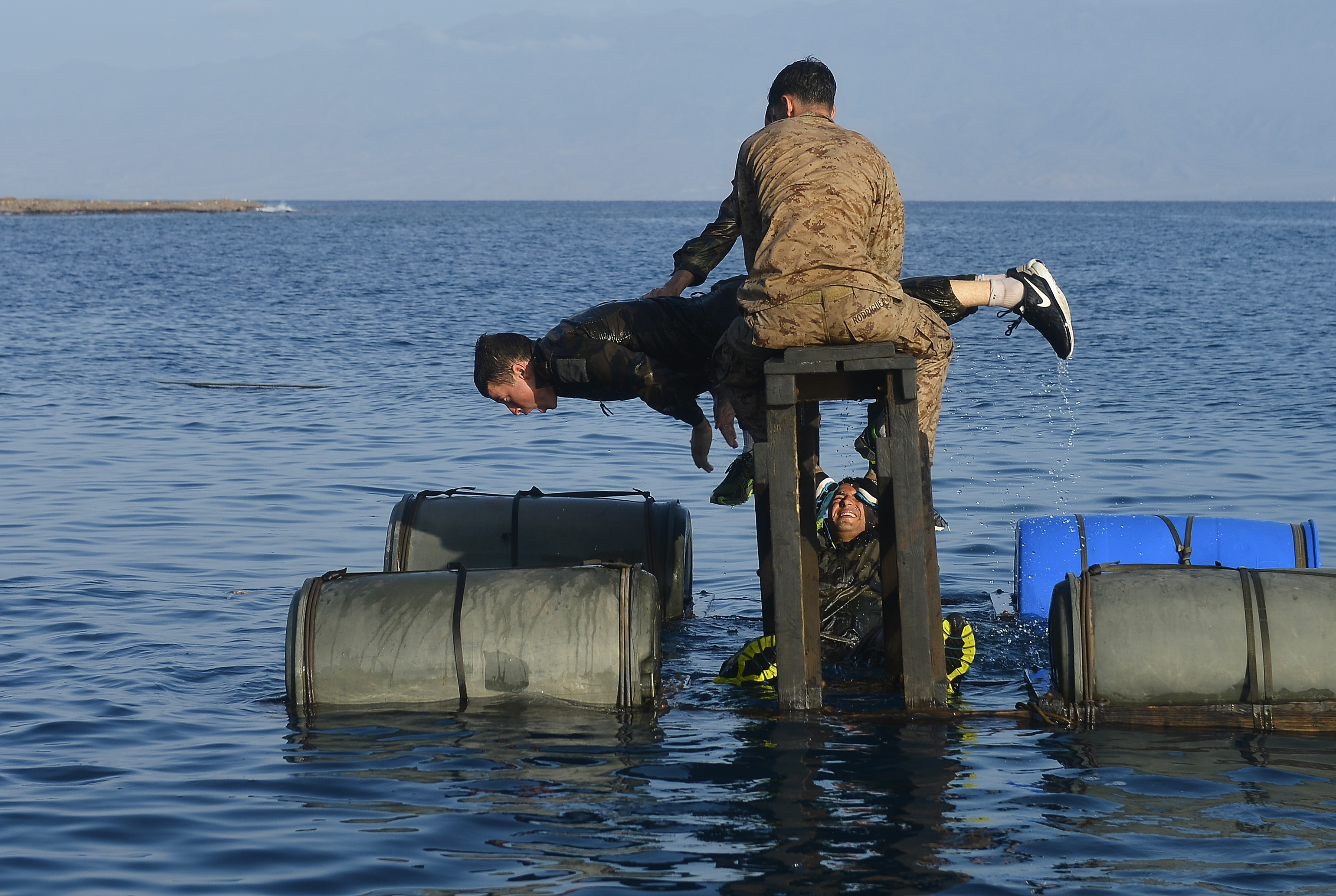 U.S. and French service members assist each other over water obstacles during the French Desert Survival Course, near Arta Beach, Djibouti, Sept. 30, 2015. French and U.S. military members worked together to learn combat lifesaving skills, field tactics, land navigation, weapons training, trap setting, and survival cooking and water source locating during the 14-day course. (U.S. Air Force photo by Senior Airman Nesha Humes)