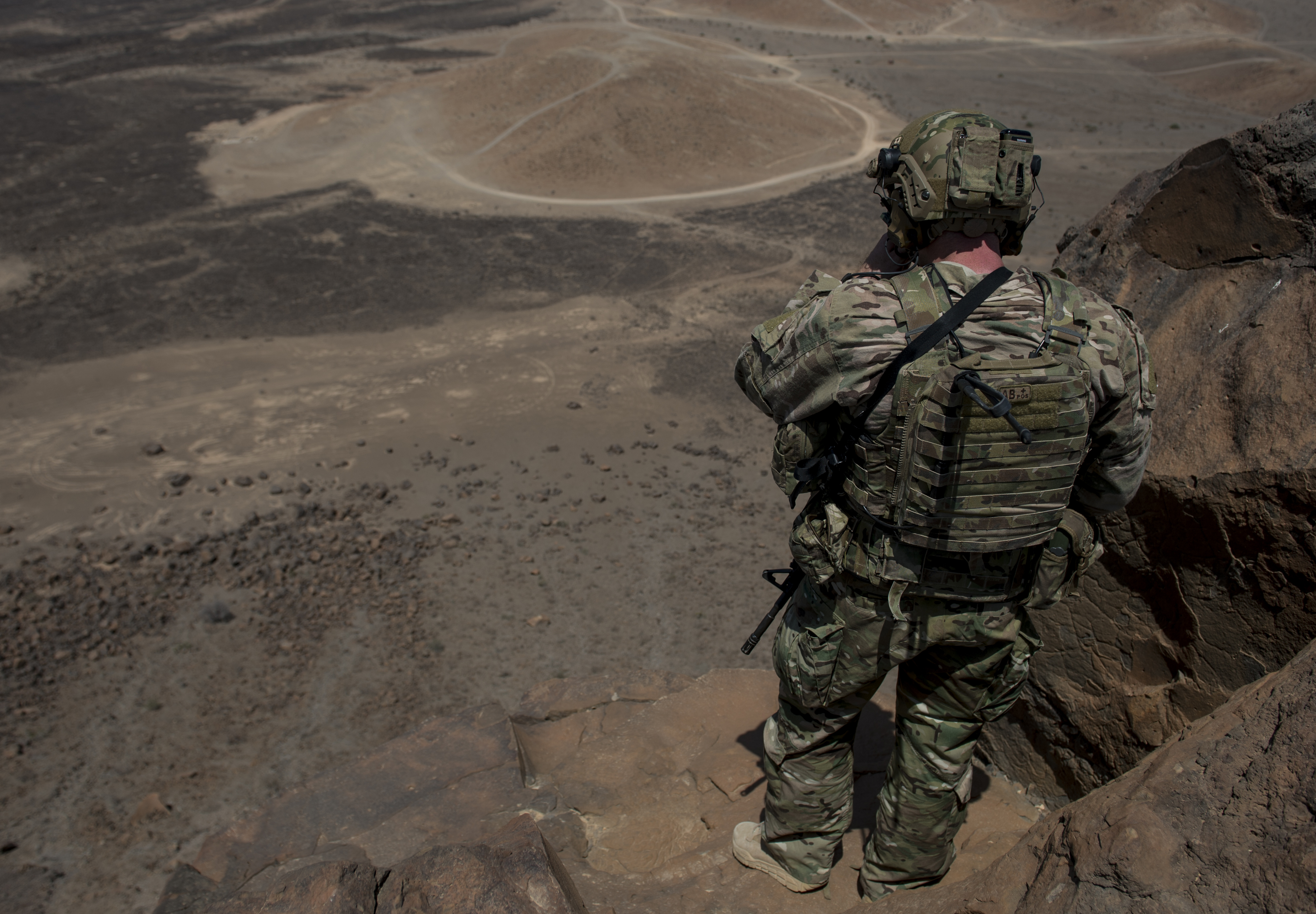 A U.S. Air Force joint terminal attack controller stands atop a cliff overlooking a mortar range Oct. 12, 2015, in Arta, Djibouti. The JTAC participation in the training added realistic joint interaction, similar to a combat environment. (U.S. Air Force photo by Senior Airman Peter Thompson/Released)