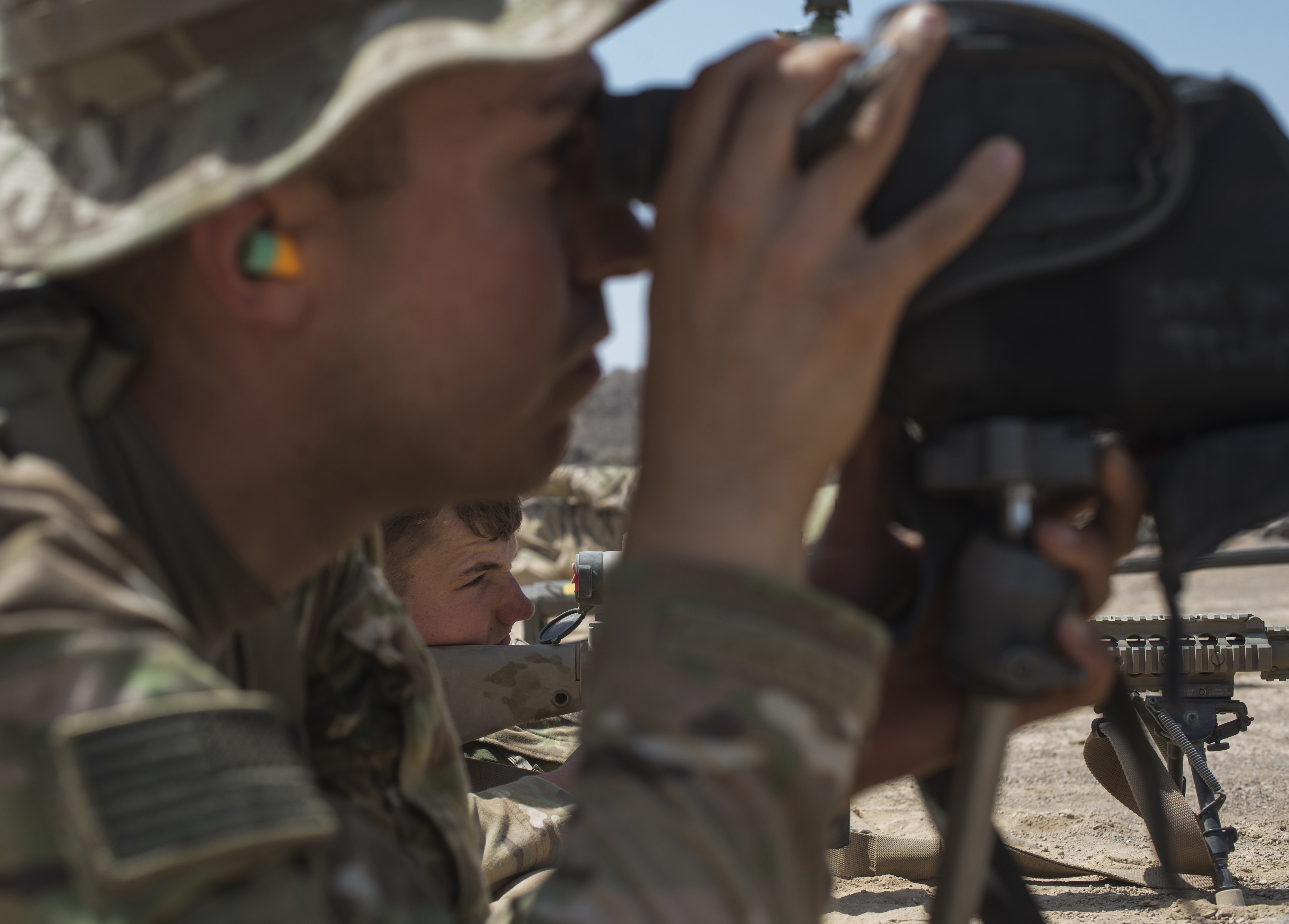 U.S. Army Pfc. Alex Kot, radio transmission operator, front, spots bullet impact points as Pfc. Conner Gillem, M240 gunner, both assigned to Alpha Company, 3rd Battalion, 15th Infantry Regiment, fires a M110 Oct. 14, 2015, in Arta, Djibouti. Scout snipers from Alpha Company participated in 40 hours of classroom instruction followed by live fire training with multiple sniper rifles. (U.S. Air Force photo by Senior Airman Peter Thompson/Released)