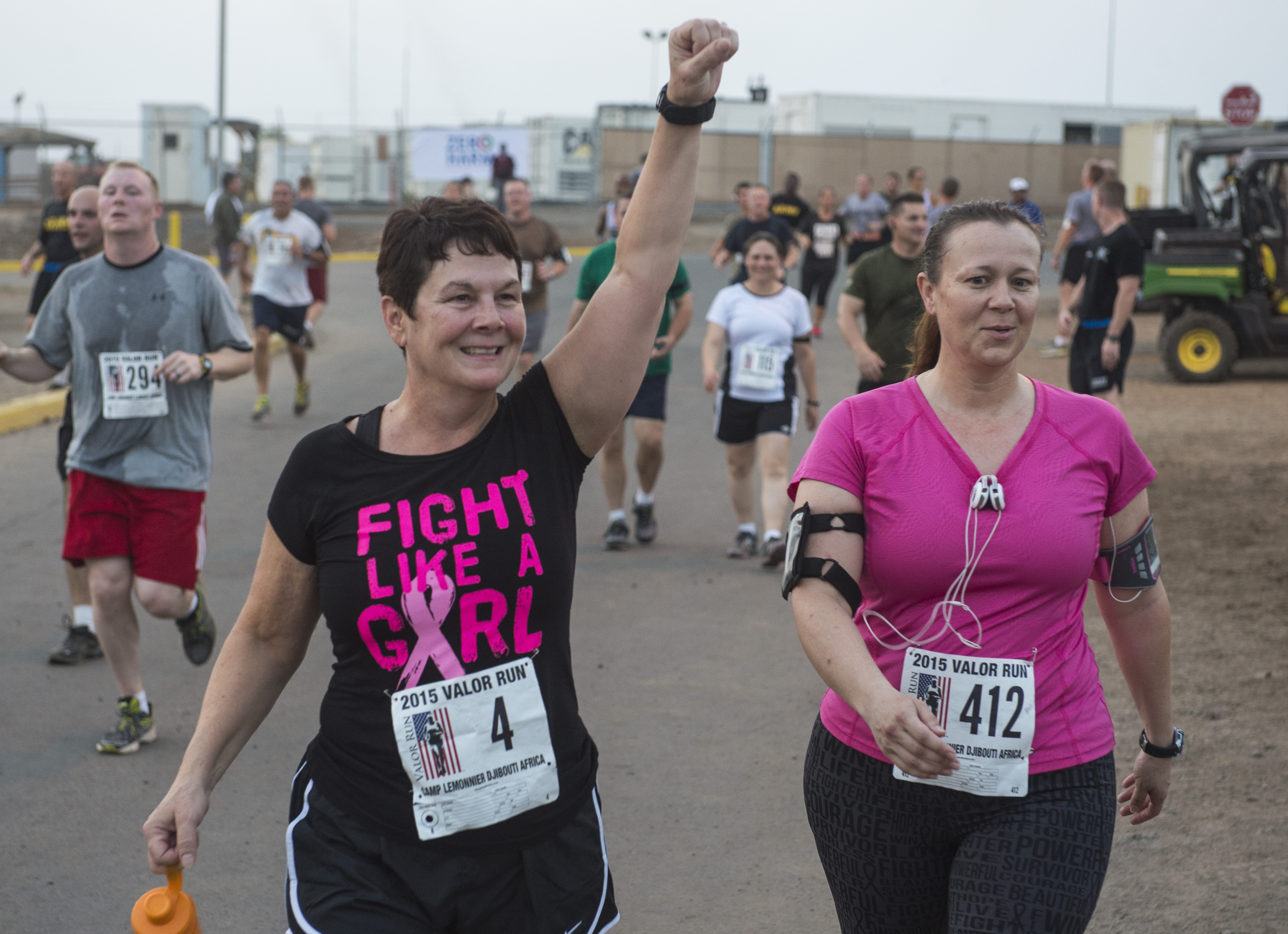 U.S. Navy Capt. Claire Bedford, Combined Joint Task Force-Horn of Africa director of personnel (left), and Air Force Lt. Col. Lynn Plunckett, CJTF-HOA Knowledge Management Operations director (right), celebrate as they cross the finish line Oct. 21, 2015, at Camp Lemonnier, Djibouti. More than 800 runners and walkers participated in a Valor Run hosted by Combined Joint Task Force-Horn of Africa and Camp Lemonnier, dedicated to fallen service women.(U.S. Air Force photo by Senior Airman Peter Thompson/Released)