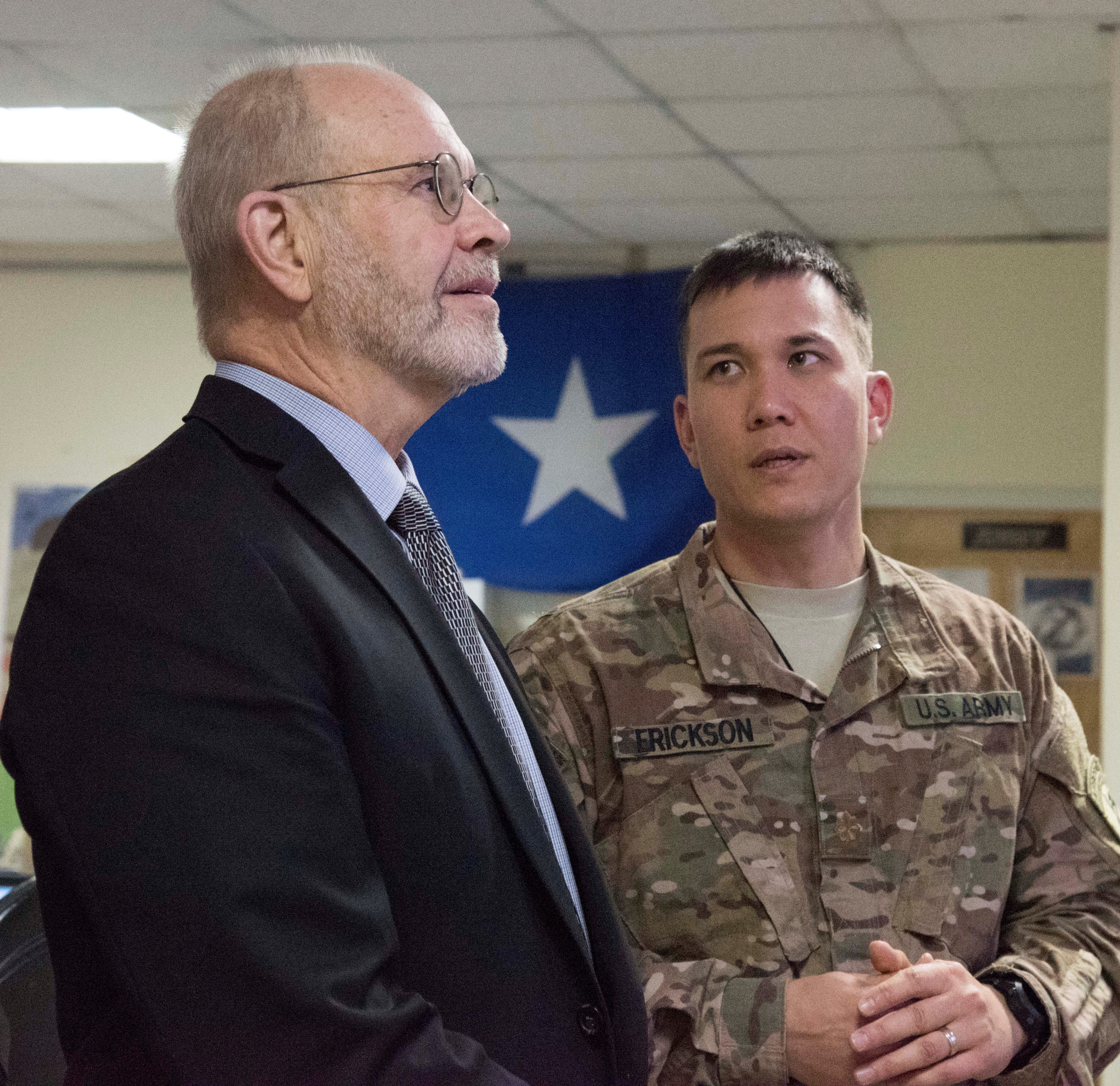 Retired Ambassador David Kaeuper, U.S. Chargé d'Affaires to Somalia hears an explanation from U.S. Army Maj. Kristopher Erickson, Somalia desk lead for the Fusion Action Cell hive at Camp Lemonnier, Djibouti, Oct. 15, 2015. The FAC personnel are separated into country desks composed of subject matter experts and foreign liaison officers who are responsible for streamlining the planning and coordination of projects in their respective countries. (U.S. Air Force photo by Staff Sgt. Victoria Sneed)