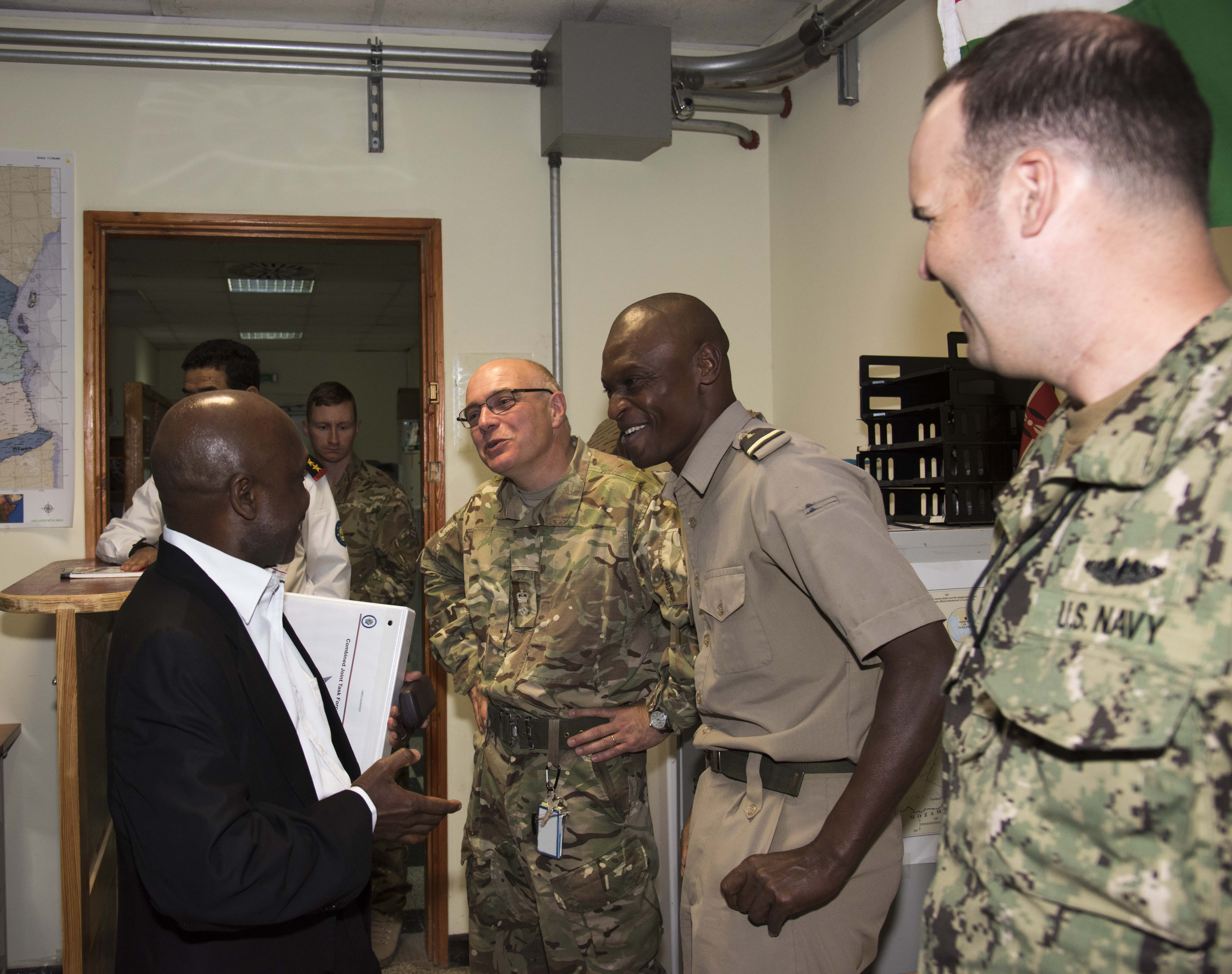 Ambassador Issimail Chanfi, Eastern Africa Standby Force (EASF) director, jokes with multinational members of the Fusion Action Cell during his tour Oct. 27, 2015 at Camp Lemonnier, Djibouti. The FAC brings representatives from regional partners into a single office where foreign liaison officers and their counterparts work, interact, plan and learn from each other. (U.S. Air Force photo by Staff Sgt. Victoria Sneed)