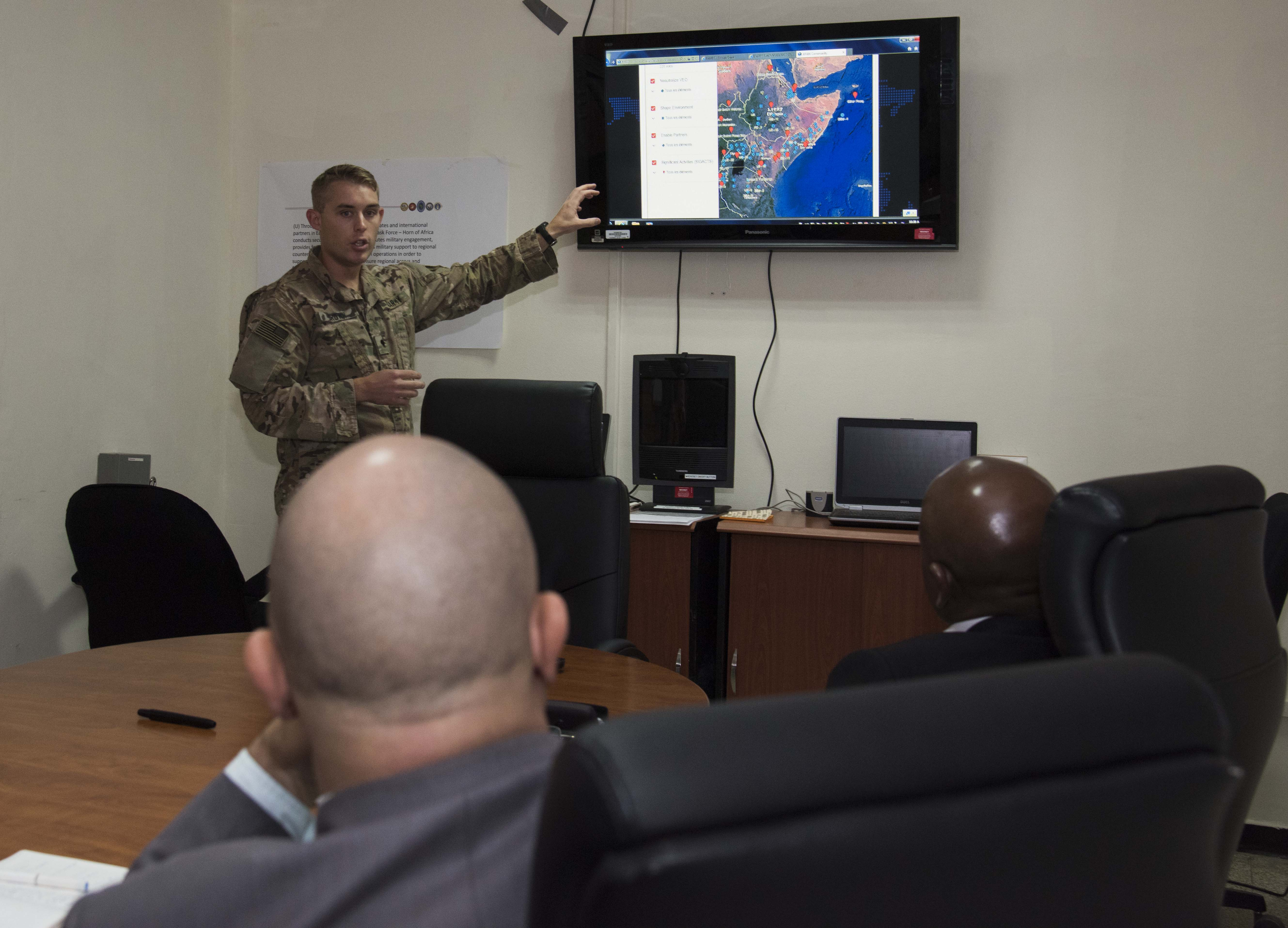 Spc. Scott Brown explains the All Partners Access Network (APAN) to Ambassador Issimail Chanfi, Eastern Africa Standby Force (EASF) director, and Benediste Hoareau, EASF head of political affairs, during their tour of Combined Task Force-Horn of Africa Oct. 27, 2015 at Camp Lemonnier, Djibouti. APAN is an information sharing service for the U.S. Department of Defense (DOD), allowing partners to share information around the globe. (U.S. Air Force photo by Staff Sgt. Victoria Sneed)