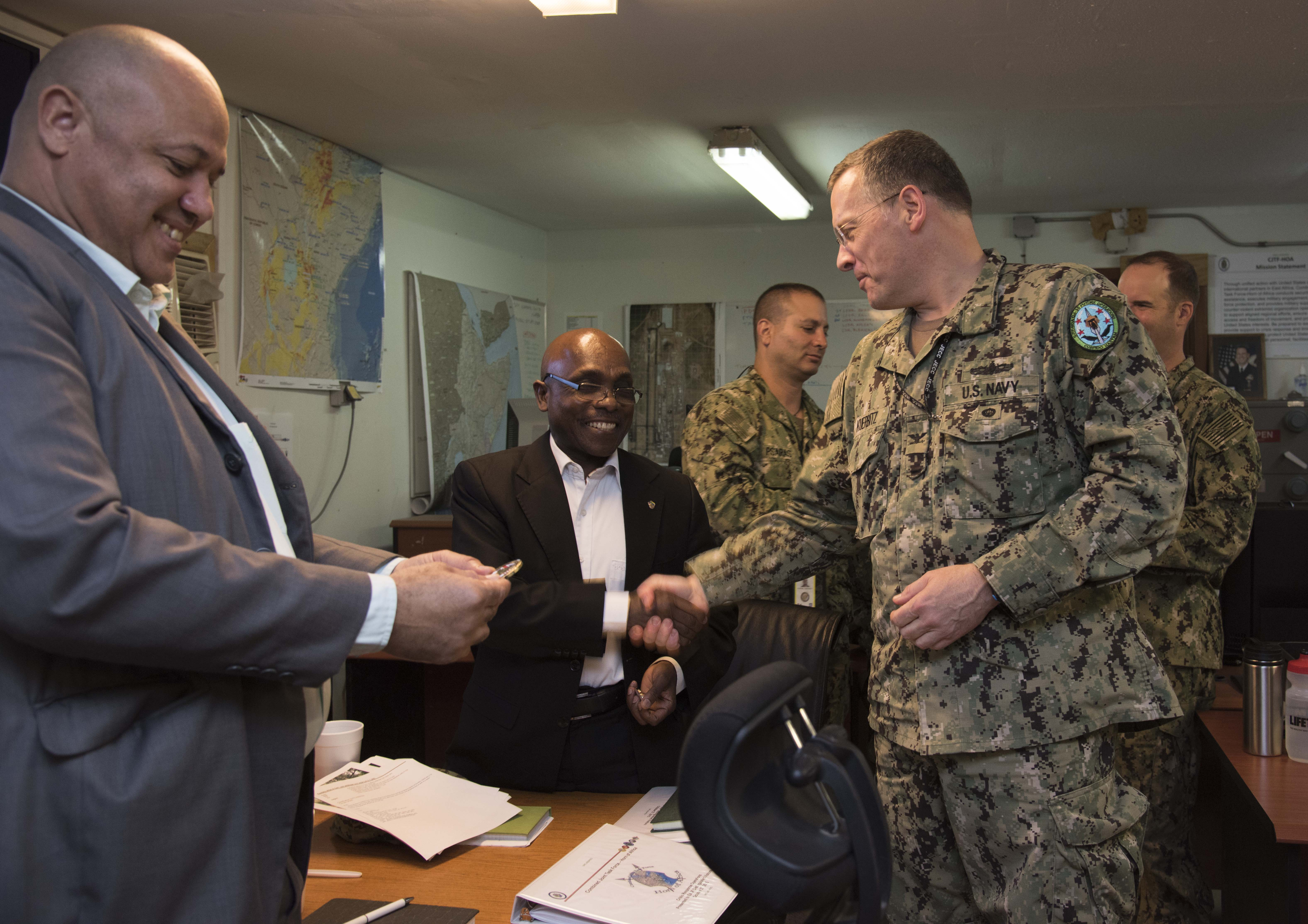 U.S. Navy Capt. Brian Kuerbitz coins Ambassador Issimail Chanfi, Eastern Africa Standby Force (EASF) director, and Benediste Hoareau, EASF head of political affairs, during their tour of Combined Task Force-Horn of Africa Oct. 27, 2015 at Camp Lemonnier, Djibouti. Coins are given as a token of thanks for continued partnership and cooperation. (U.S. Air Force photo by Staff Sgt. Victoria Sneed)
