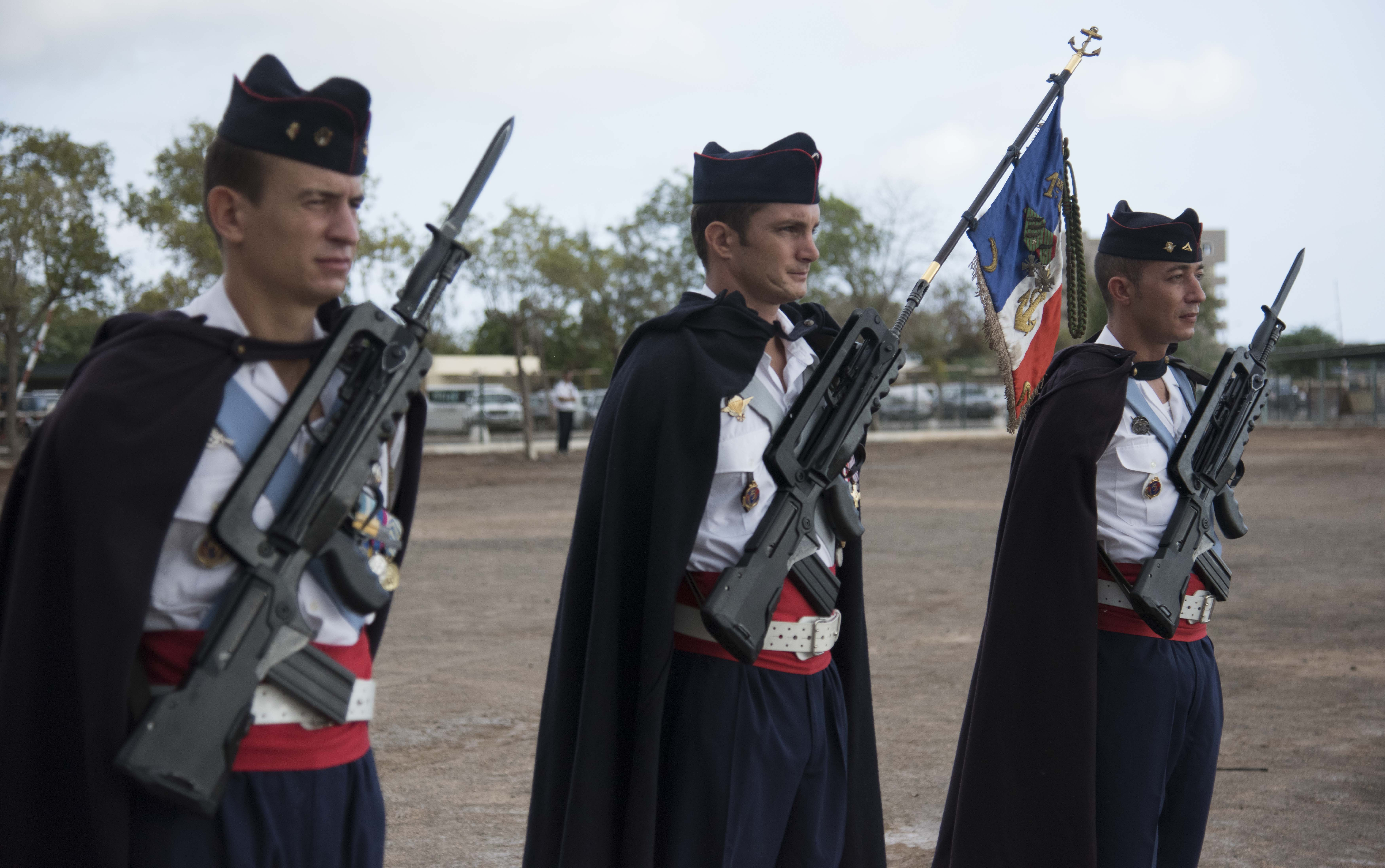 French troops stand guard over the flag of the French Somali Battalion during the Armistice Day ceremony at the French Marine Base, Nov. 11, 2015. Troops from the Horn of Africa and Yemen carried the flag through both world wars.