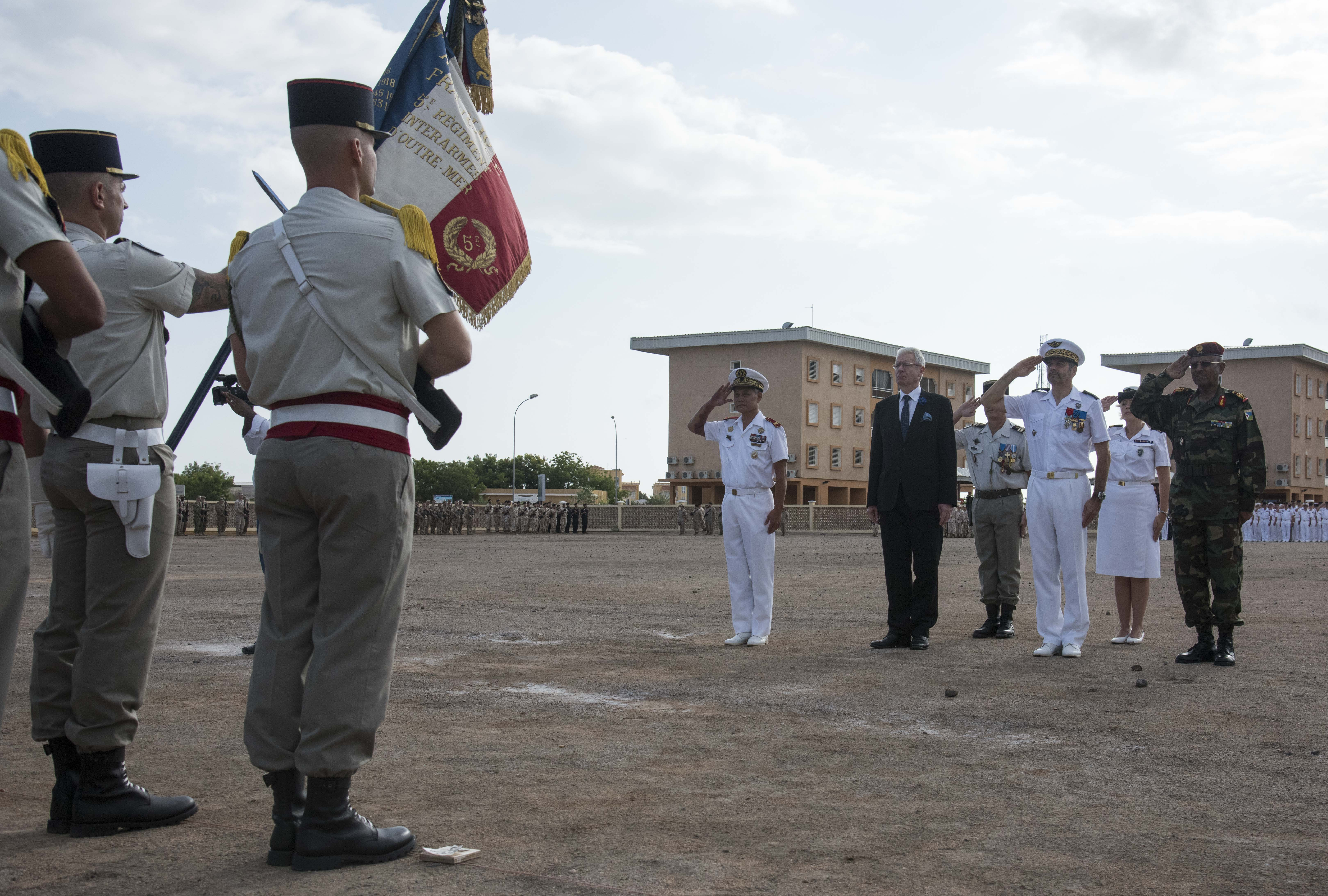The officiating party salutes the colors of the 5th Foreign Infantry Regiment during the Armistice Day ceremony at the French Marine Base, Nov. 11, 2015. The ceremony commemorated the end of hostilities in World War I.