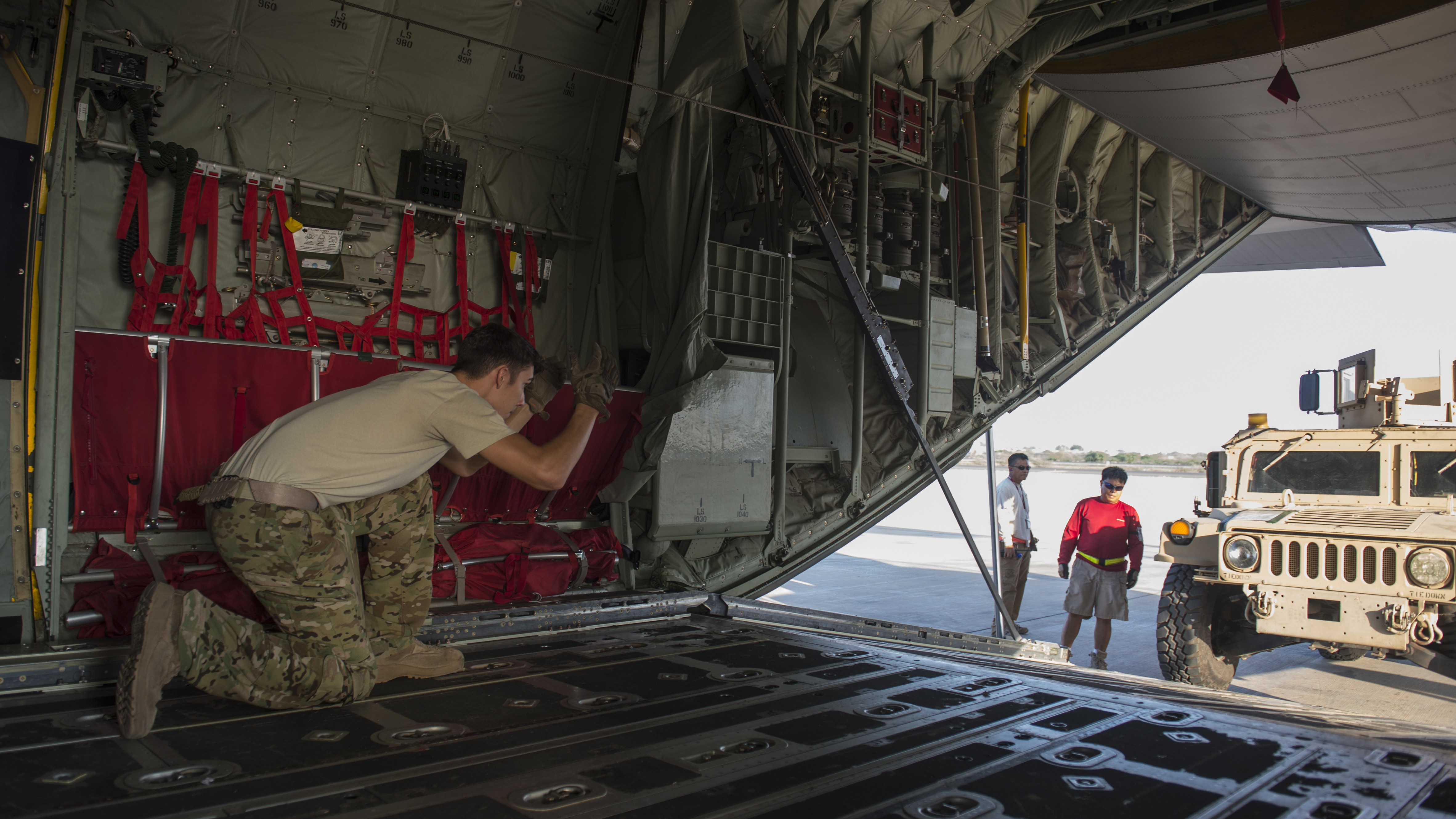 Senior Airman Zachary McGhee, 75th Expeditionary Airlift Squadron loadmaster, directs a Charlie Co. 2-124 up-armored Humvee into a C-130J Super Hercules Nov. 24, 2015, at Camp Lemonnier, Djibouti. The vehicle was delivered to a forward operating location where it will be used to conduct patrols and increase force protection posture. (U.S. Air Force photo by Senior Airman Peter Thompson)