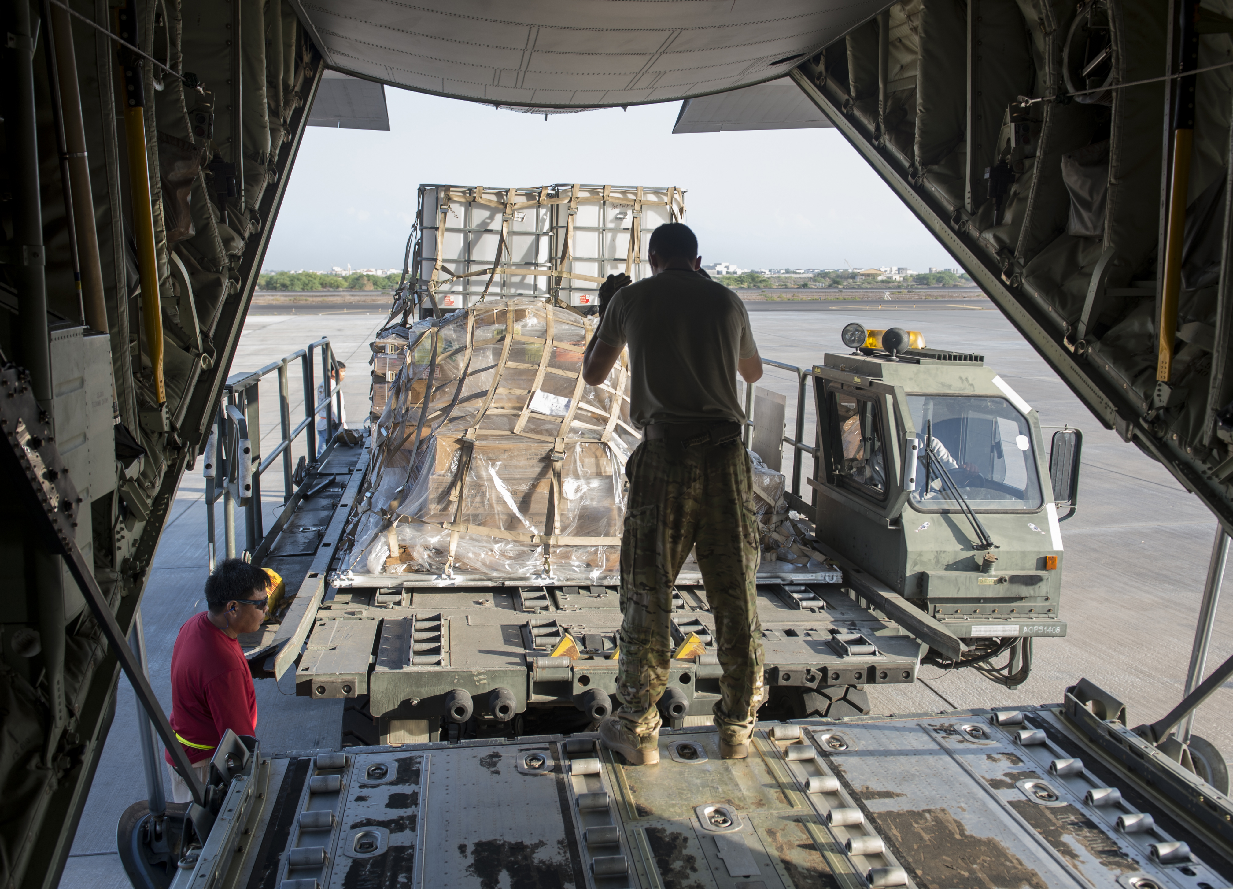 Senior Airman Zachary McGhee, 75th Expeditionary Airlift Squadron loadmaster, directs a K Loader behind a C-130J Super Hercules Nov. 24, 2015, at Camp Lemonnier, Djibouti. The shipment, which consisted of a Humvee and equipment, is one of several coordinated shipments between Combined Joint Task Force-Horn of Africa's Joint Logistics Operations Center and the 75th EAS. (U.S. Air Force photo by Senior Airman Peter Thompson)