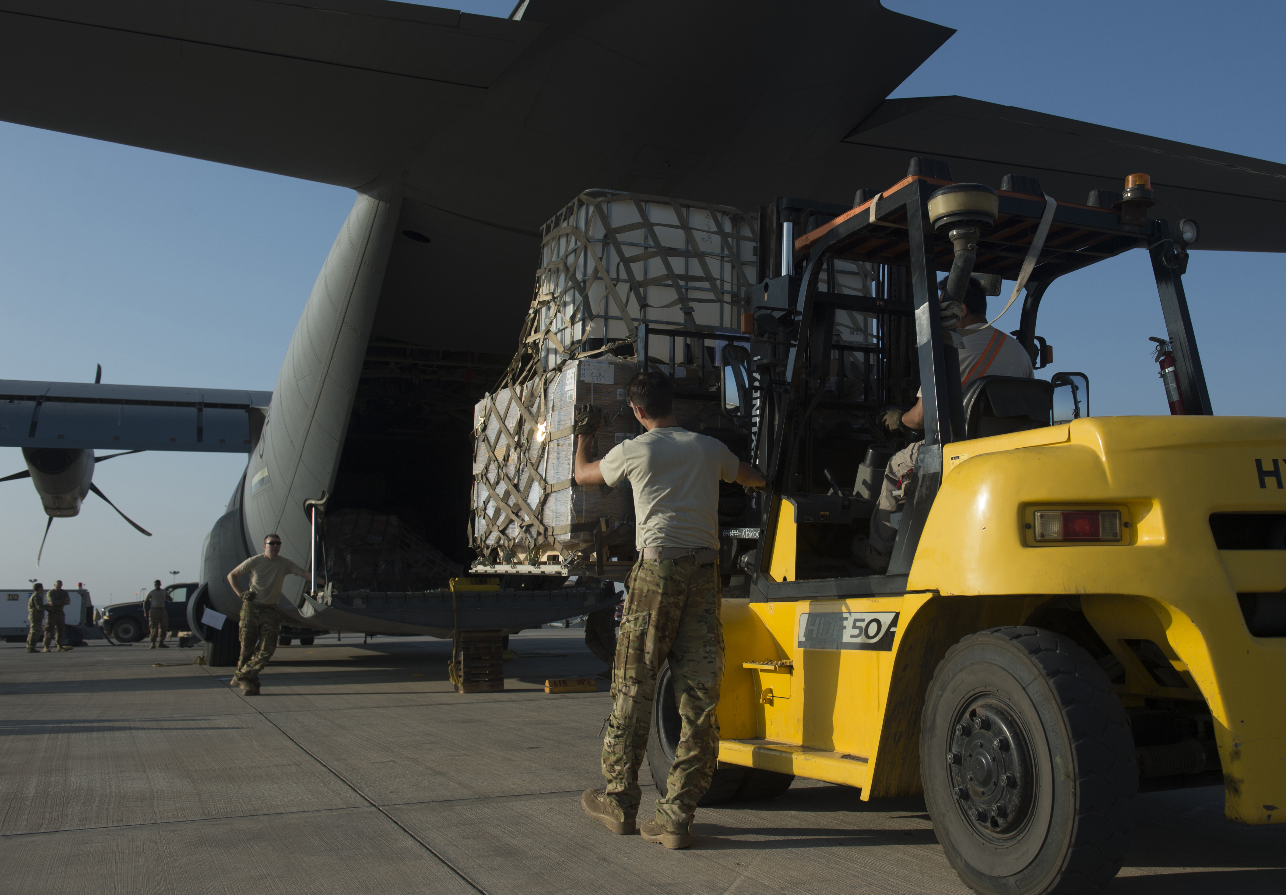 Senior Airman Zachary McGhee, 75th Expeditionary Airlift Squadron loadmaster, directs a forklift behind a C-130J Super Hercules Nov. 24, 2015, at Camp Lemonnier, Djibouti. The shipment, which consisted of a Humvee and equipment, is one of several coordinated shipments between Combined Joint Task Force-Horn of Africa's Joint Logistics Operations Center and the 75th EAS. (U.S. Air Force photo by Senior Airman Peter Thompson)