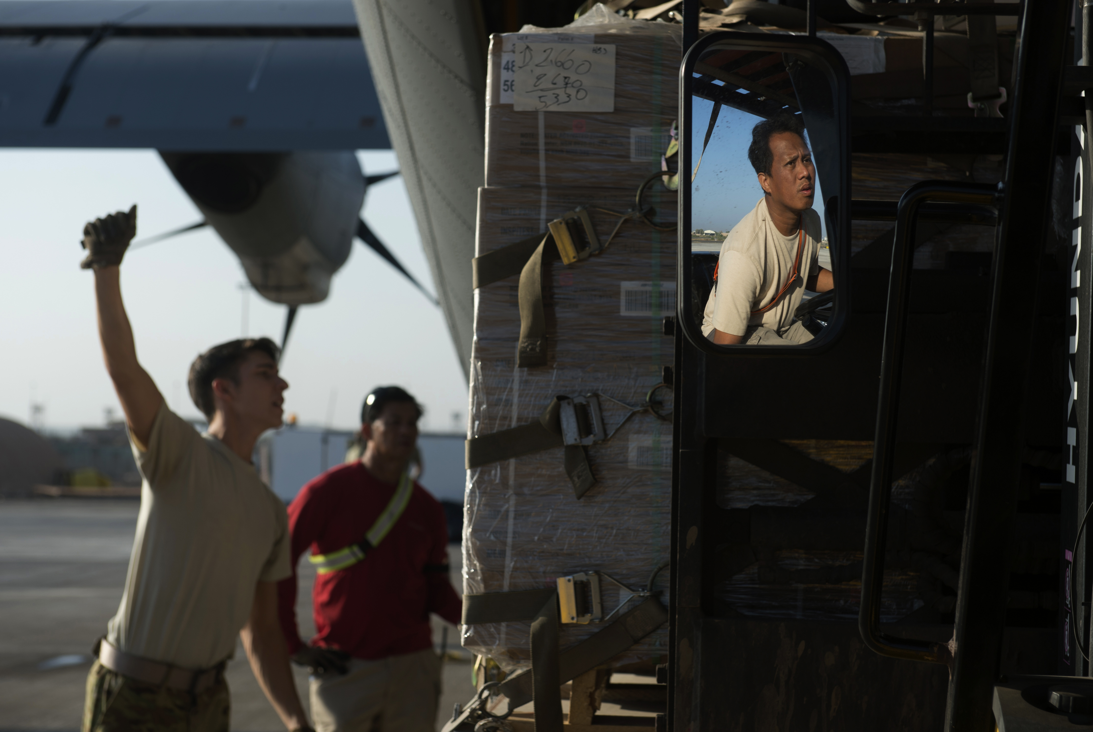 Senior Airman Zachary McGhee, 75th Expeditionary Airlift Squadron loadmaster, uses hand signals to communicate directions with a forklift behind a C-130J Super Hercules Nov. 24, 2015, at Camp Lemonnier, Djibouti. The 75th EAS' C-130J aircrews fly a wide range of missions, including the timely movement of the East Africa Response Force in support of Combined Joint Task Force-Horn of Africa.  (U.S. Air Force photo by Senior Airman Peter Thompson)