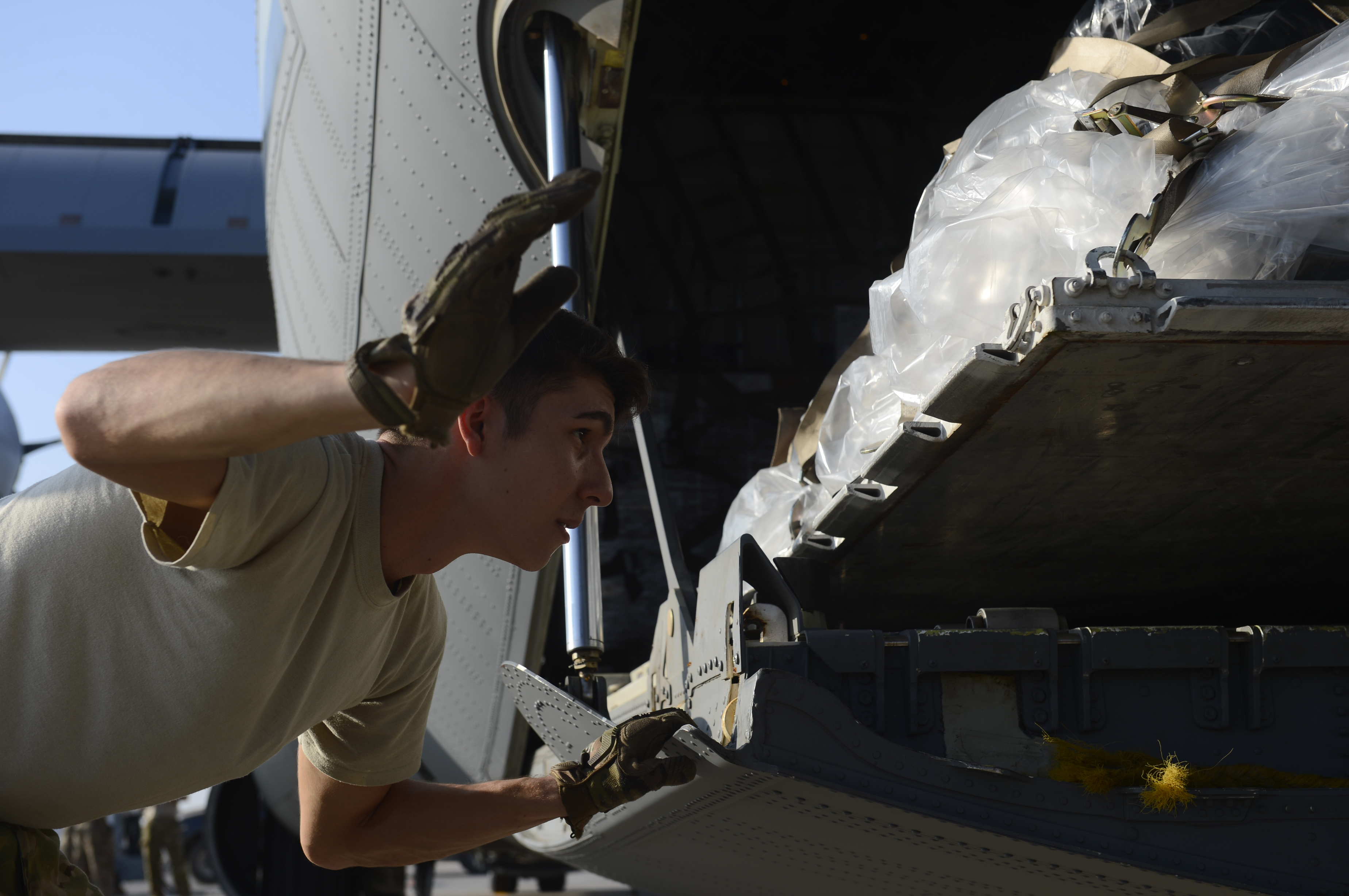 Senior Airman Zachary McGhee, 75th Expeditionary Airlift Squadron loadmaster, instructs a forklift operator to lower cargo onto a C-130J Super Hercules Nov. 24, 2015, at Camp Lemonnier, Djibouti. The 75th EAS' C-130J aircrews fly a wide range of missions, including the timely movement of the East Africa Response Force in support of Combined Joint Task Force-Horn of Africa. (U.S. Air Force photo by Senior Airman Peter Thompson)